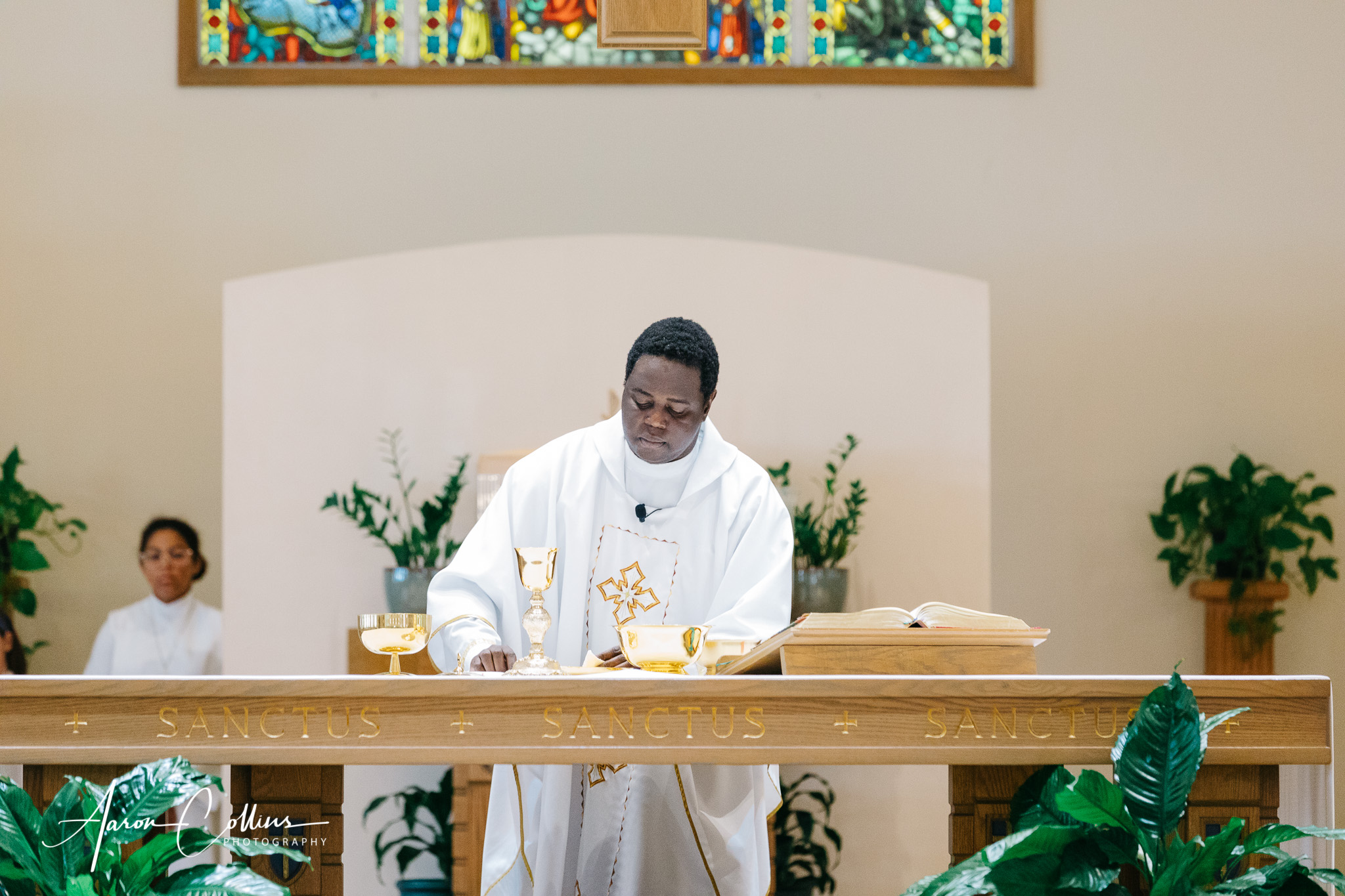 Father Charles Omolo at Saint George Parish in Worcester preparing the chalice during a wedding ceremony.