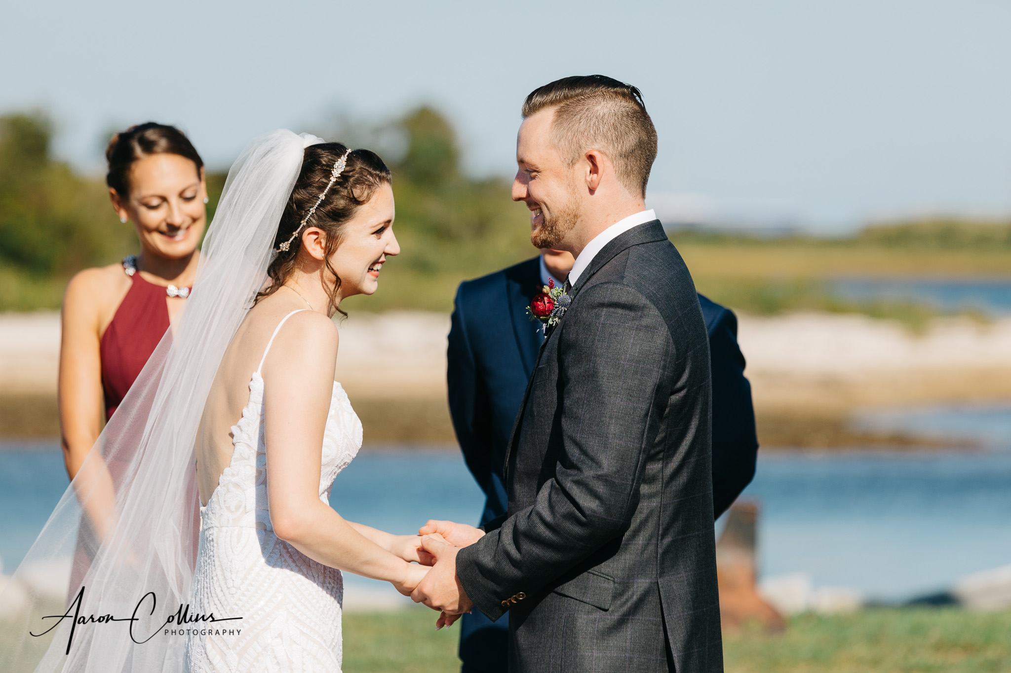 "Sunny Wedding ceremony at Block Island Maritime Institute with the bride and groom saying ""I do"" while they share a laugh."