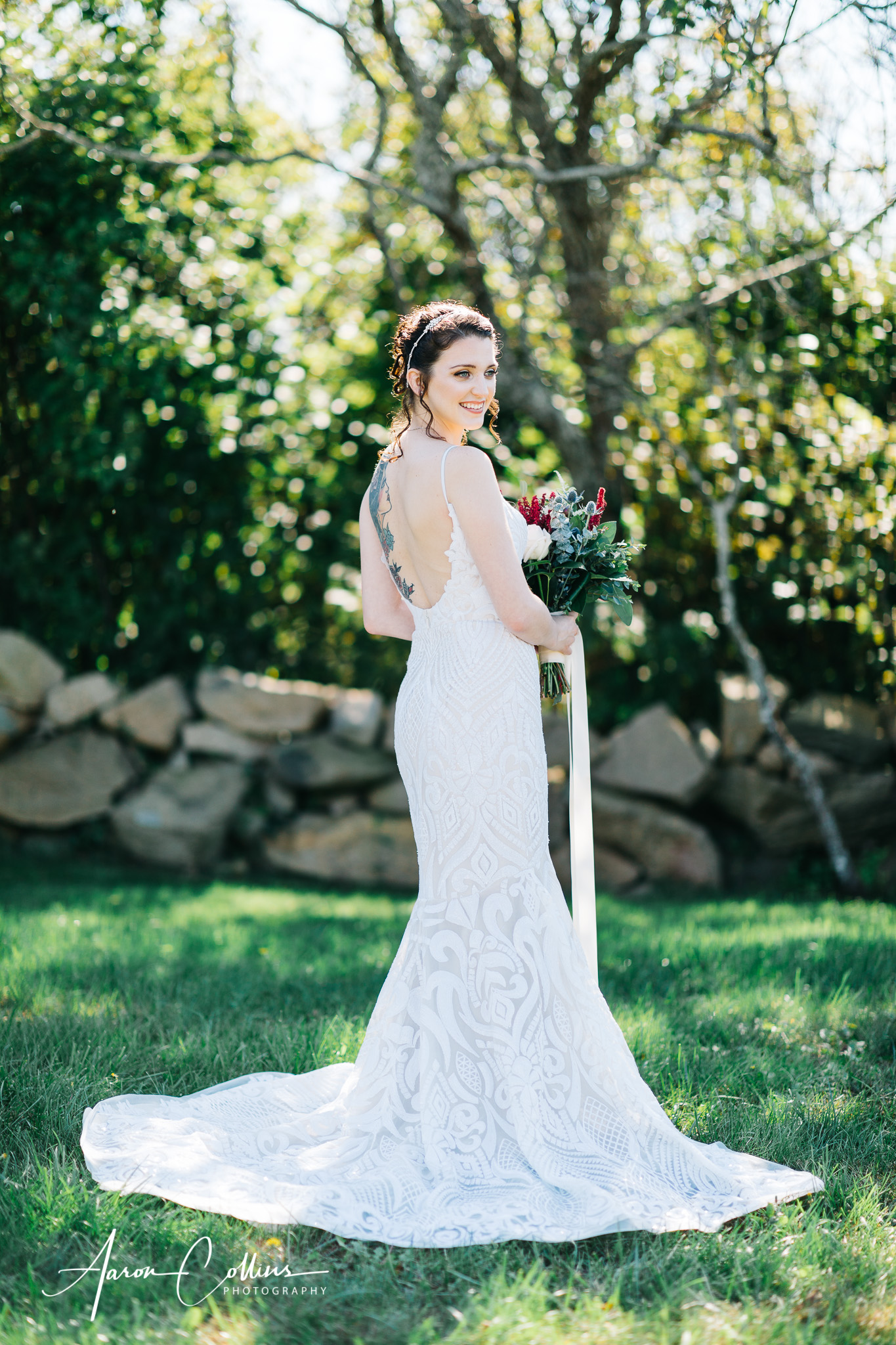 Full length portrait of the bride in her wedding dress outside in front of green leaves and grass, with her tattoo showing on the back
