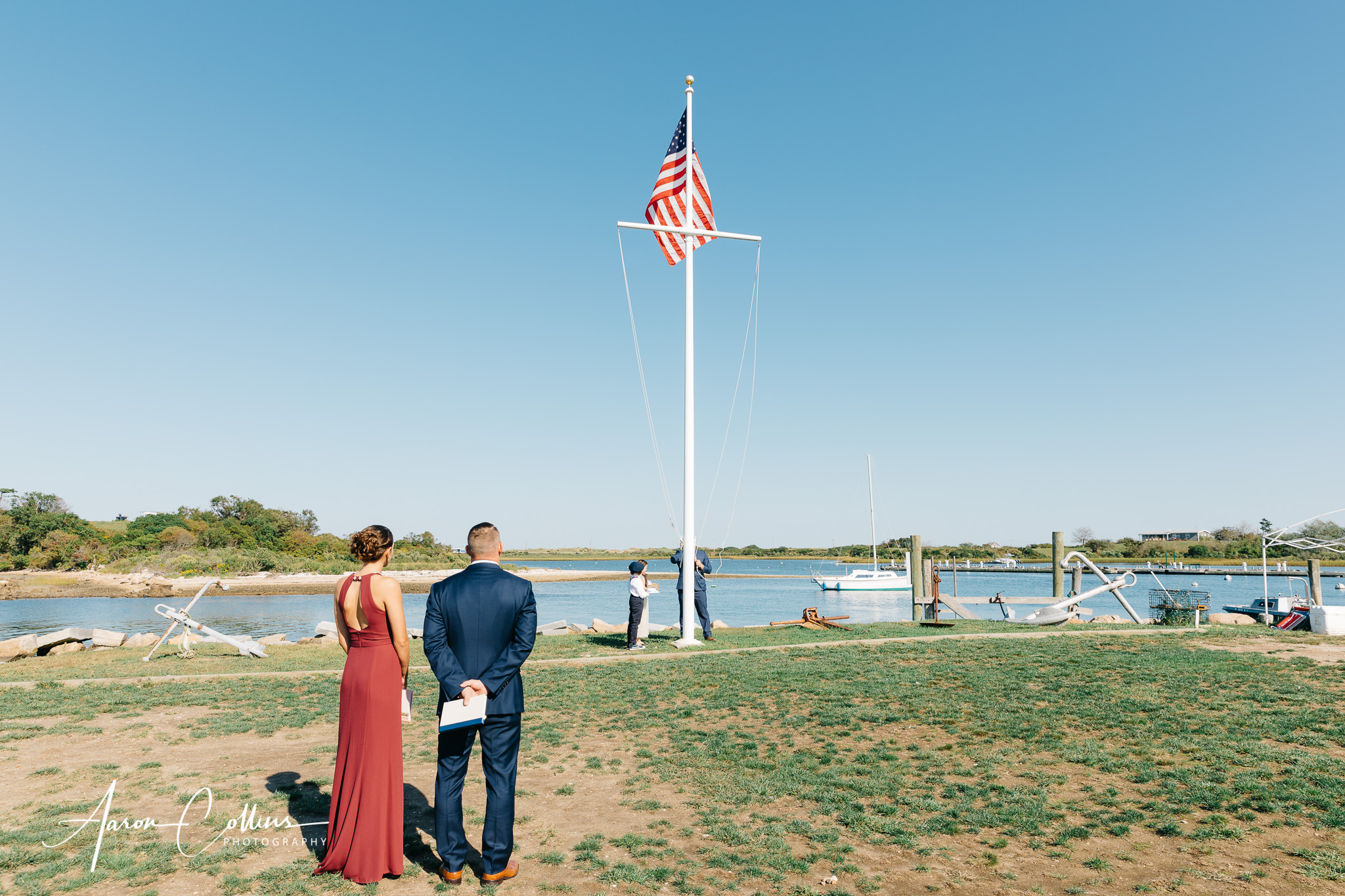 Flag is raised before the wedding ceremony begins with New Harbor Block Island and a few boats and other nautical gear visible in the background