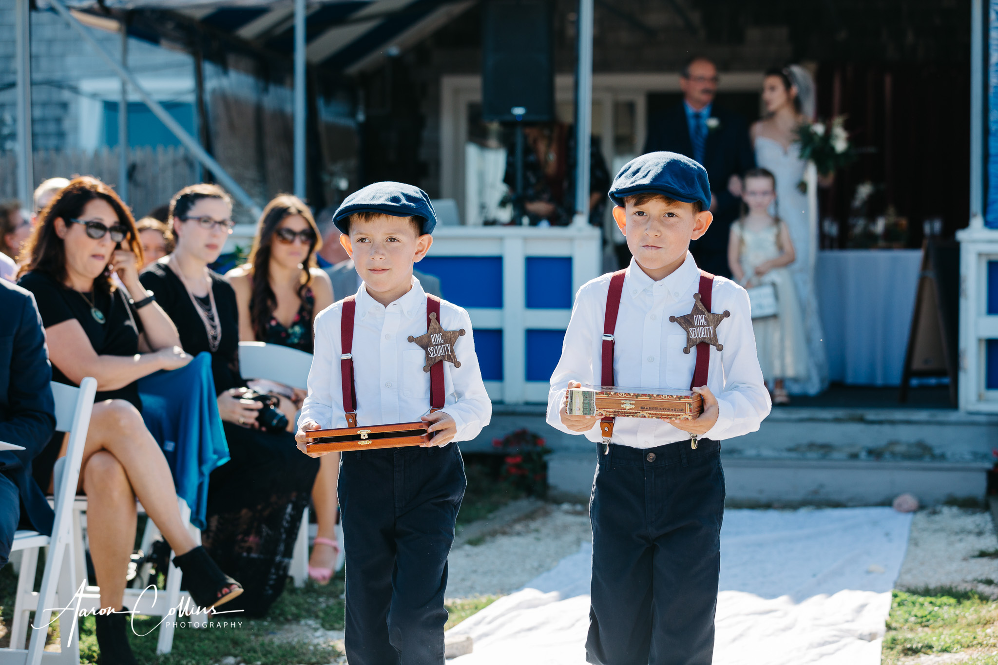 "The ring bearers, wearing ""ring security"" badges as they dress in prohibition era costumes walking down the aisle."