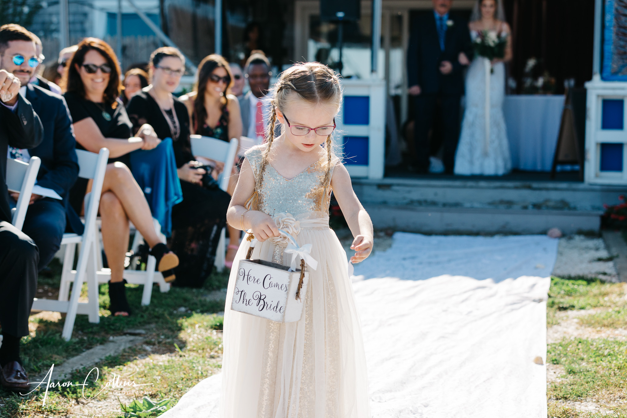 The flower girl drops petals in the aisle.