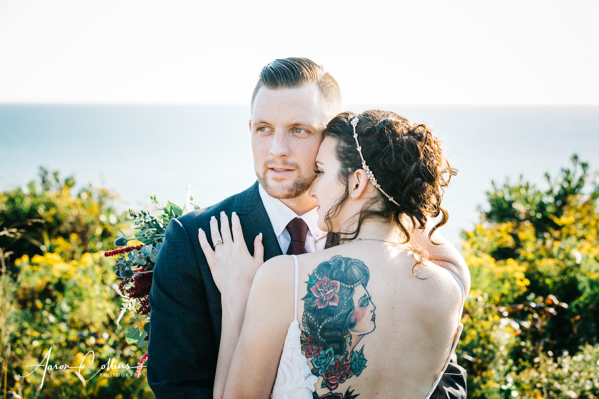 Bride facing Groom at Mohegan Bluffs on Block Island with her back tattoo visible and Block Island Sound visible in the background