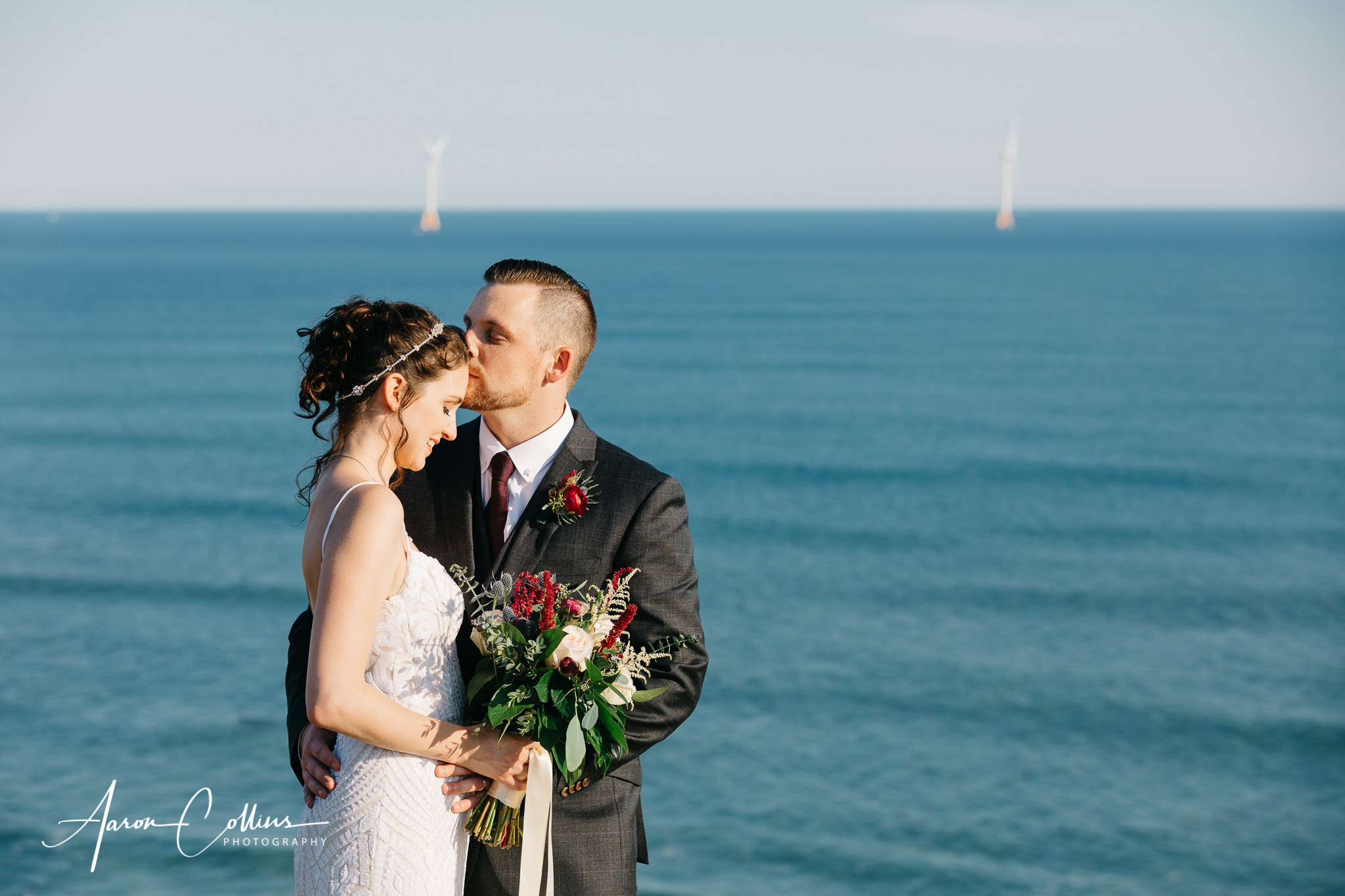 Groom kissing bride on the forehead on the cliffs at Mohegan Bluffs overlooking Block Island Sound.