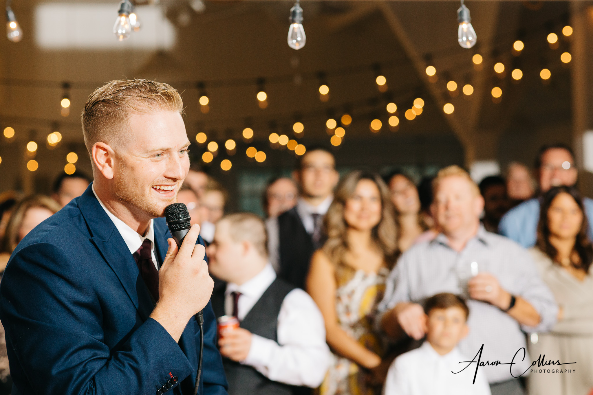 Best man giving the speech at Block Island Maritime Institute with bokeh visible in the lighting hanging in the background