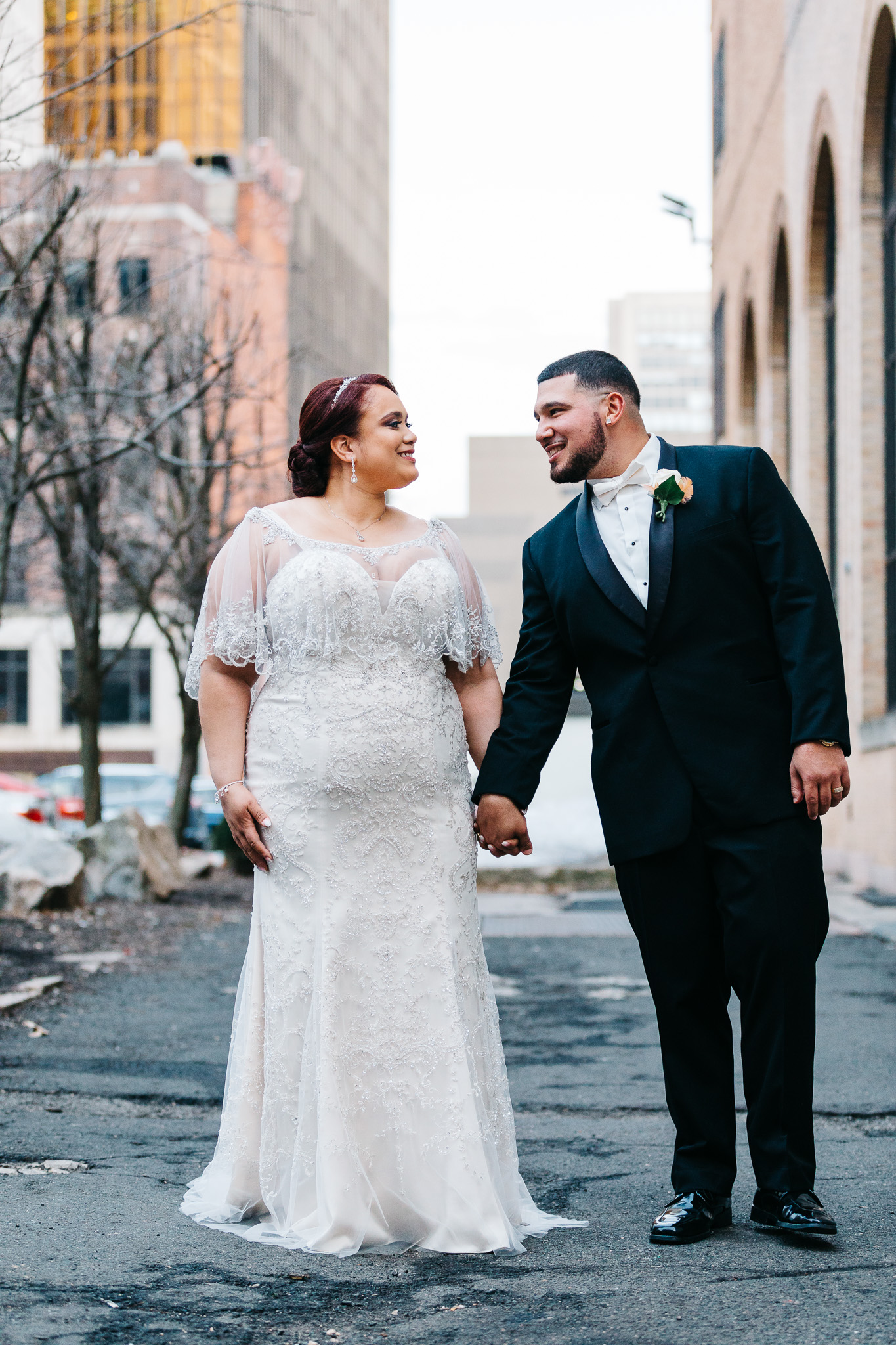 Couple standing in the driveway at the society room of hartford ct after their wedding ceremony posing for a portrait with the buildings in the background.