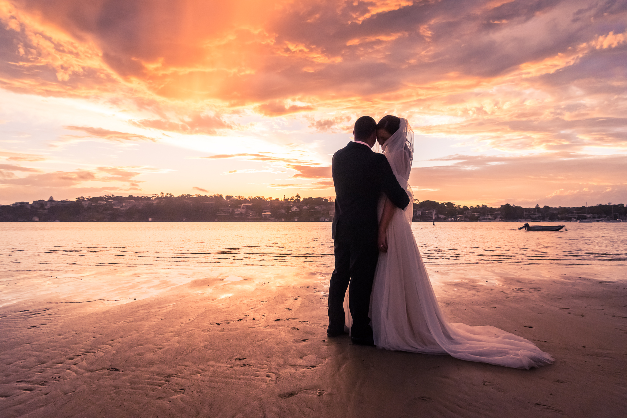 sunset on the beach with bride and groom