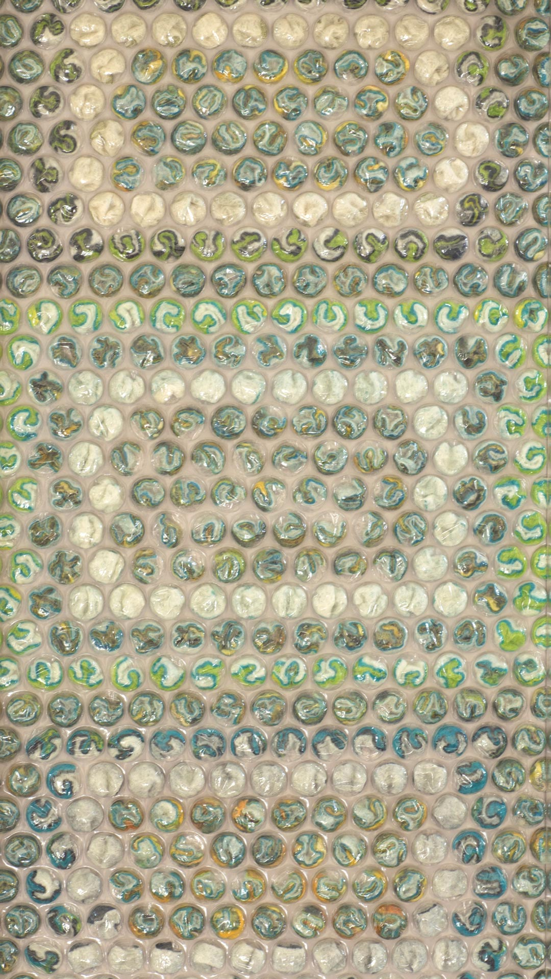 Bubble wrap textile art which features as part of Gail Hawes exhibition ROUND. All artworks featured bubble wrap filled with a variety of textiles including wool, hand made felt, silk fabric. This artwork features multi coloured,  layered hand made and hand stitched feltwithin the bubbles.