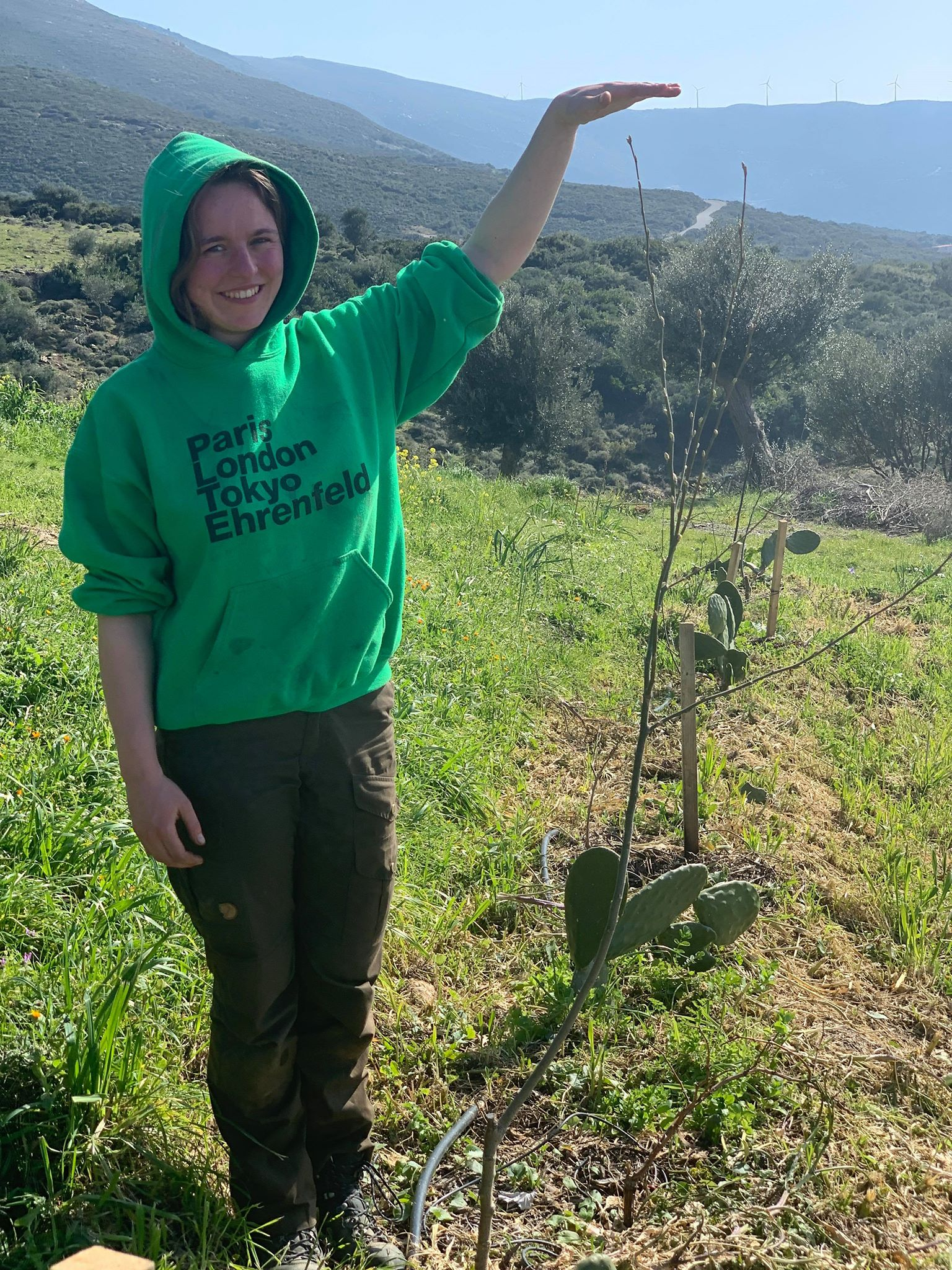 Farm volunteer, Carla Gams, standing next to one of our Poplar trees which have made enormous progress from the tiny cuttings we planted a year ago!