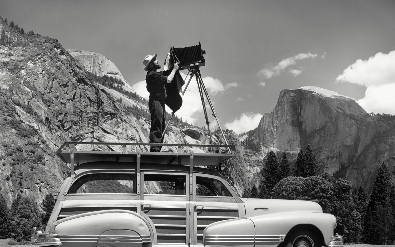 Ansel Adams using his woody wagon as a platform to set up a shoot in Yosemite National Park.