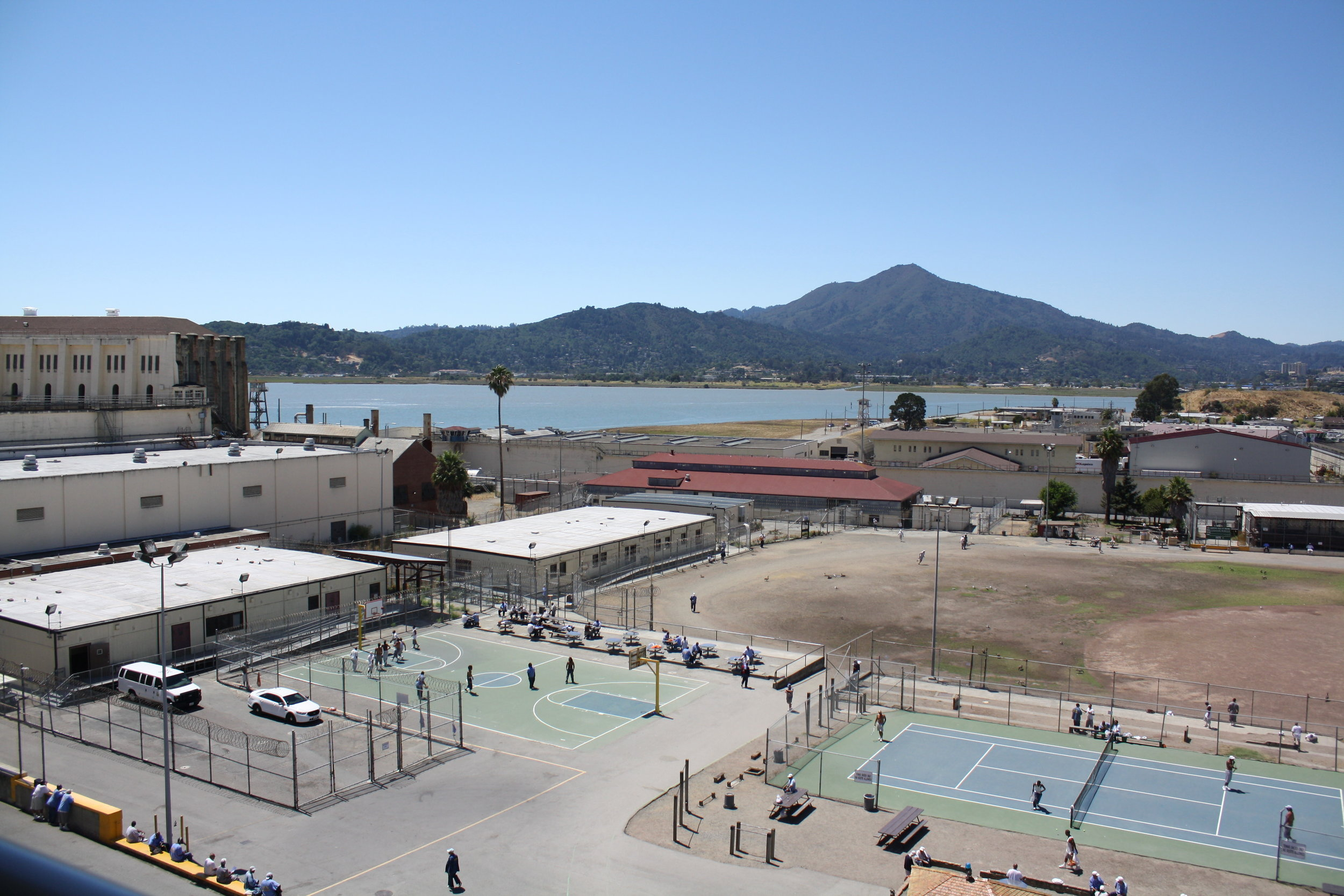 The San Quentin Yard - I've never seen it this empty, but this is where I walk across to get to the Education Center, the white rectangular building in the back. The San Quentin News newsroom is in the left corner of the building with the red roof. My first time inside, I did not expect to see a tennis court. More surprising though were the geese and ducks that usually hang out in the baseball field.