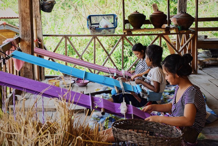 Women making cloth for handbags in Asia