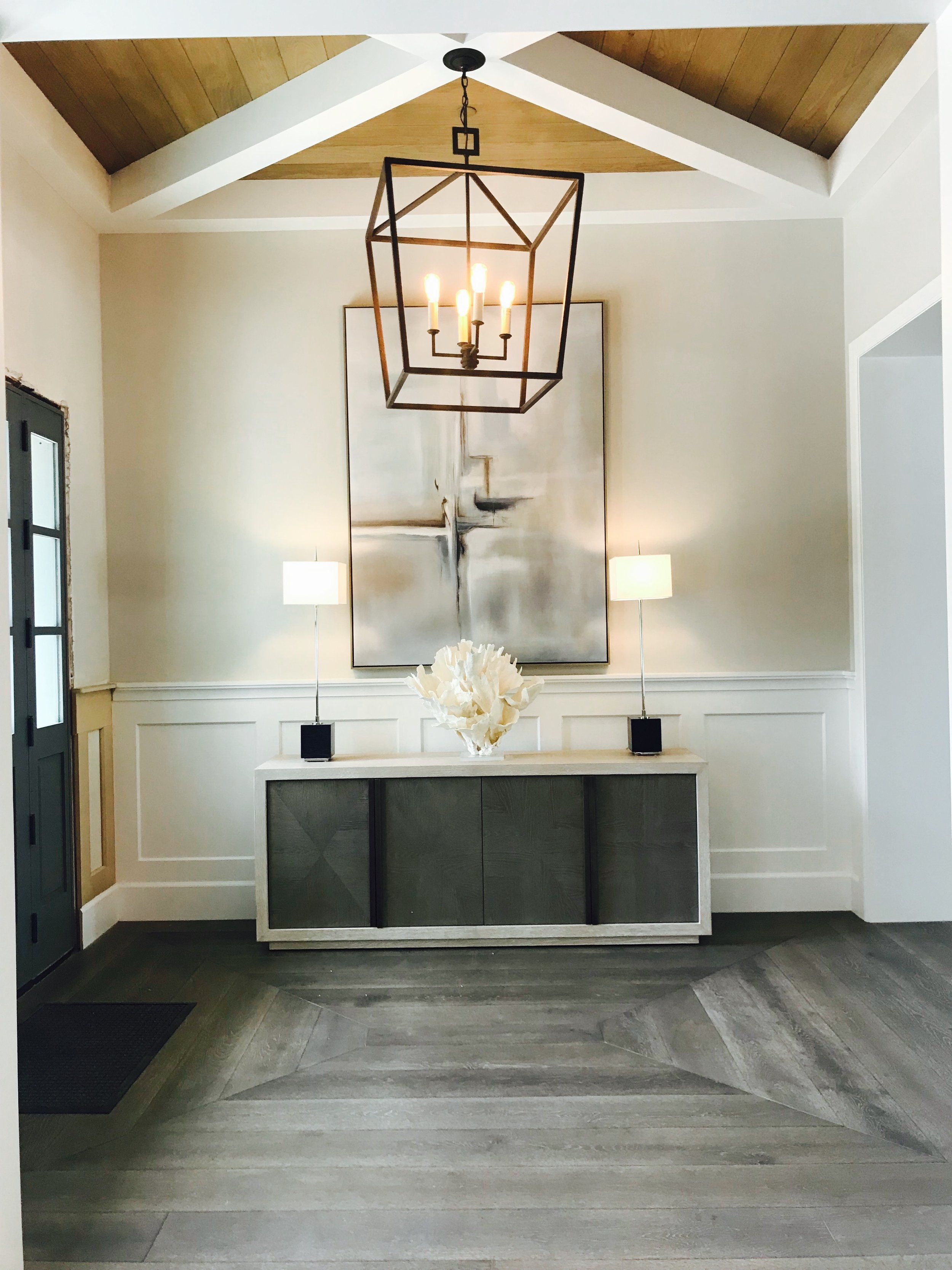 A central dark iron chandelier suspends from cross beams at the ceiling with warm wood T&G between.