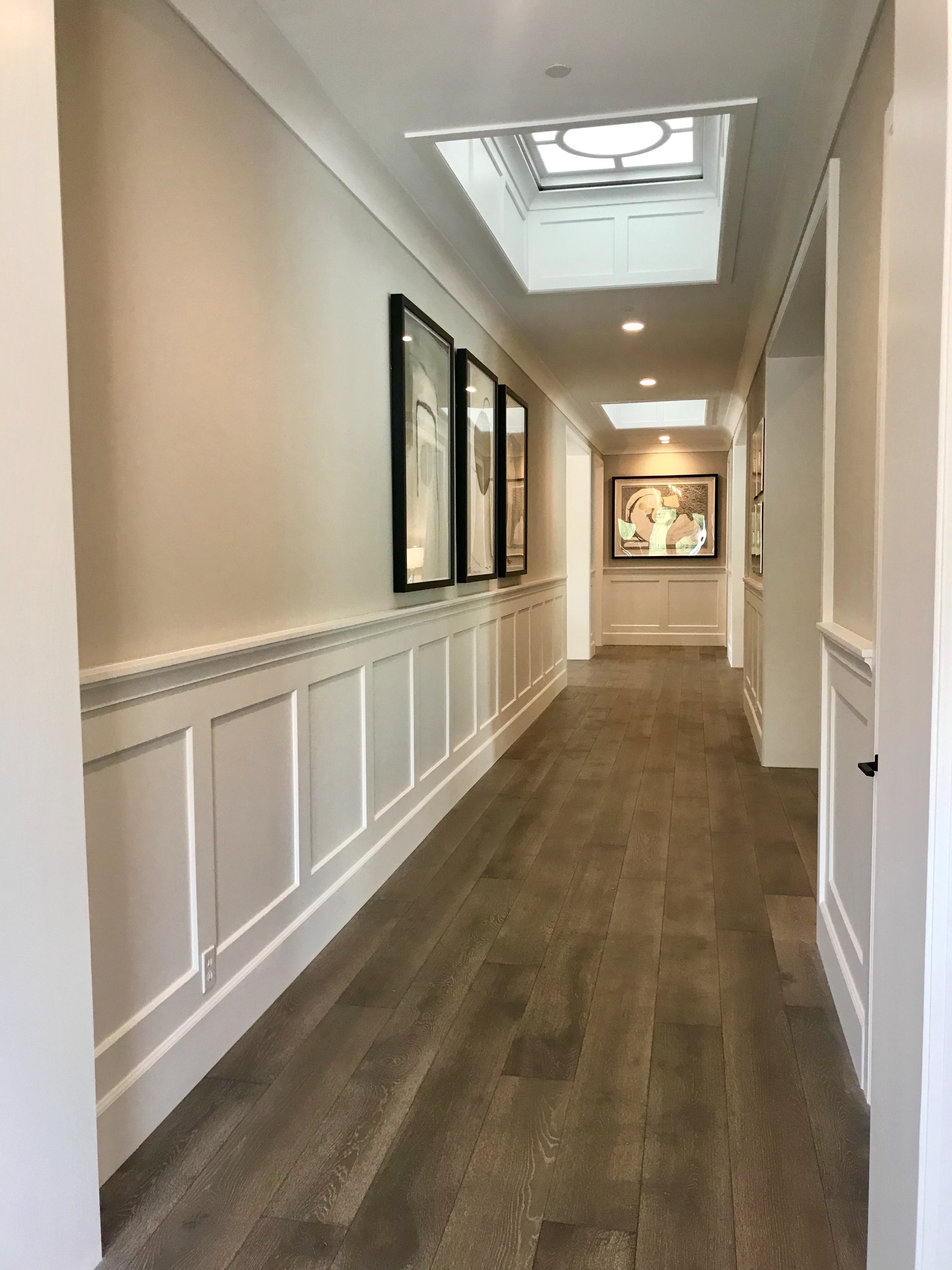 Crisp white wainscoting wraps the main hallway and a series of contemporary artwork dresses up the space.