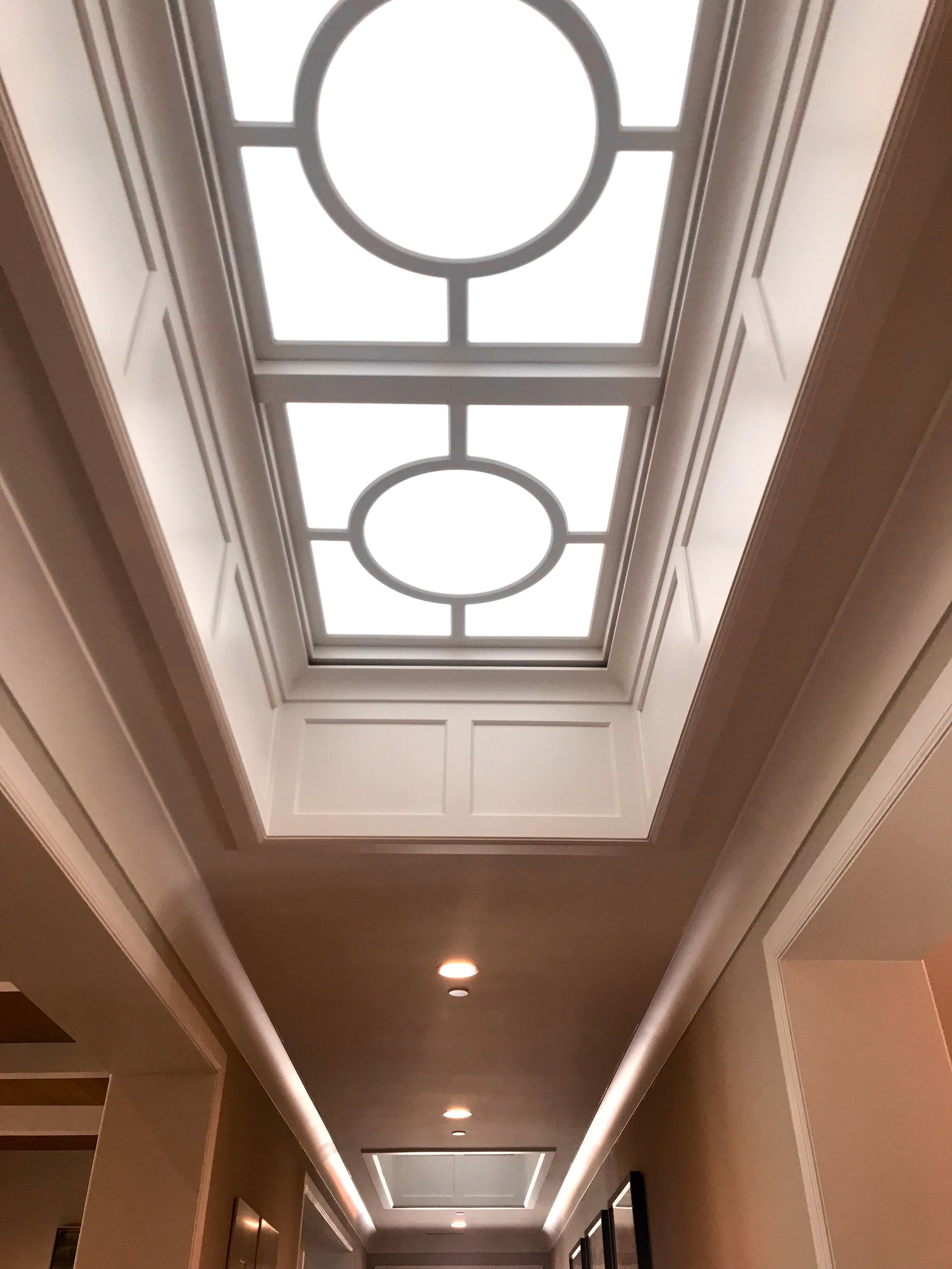 Custom skylights allow natural light along the main path of travel, paneling surrounds the sides of the ceiling alcove with circular moulding and frosted acrylic insets above.
