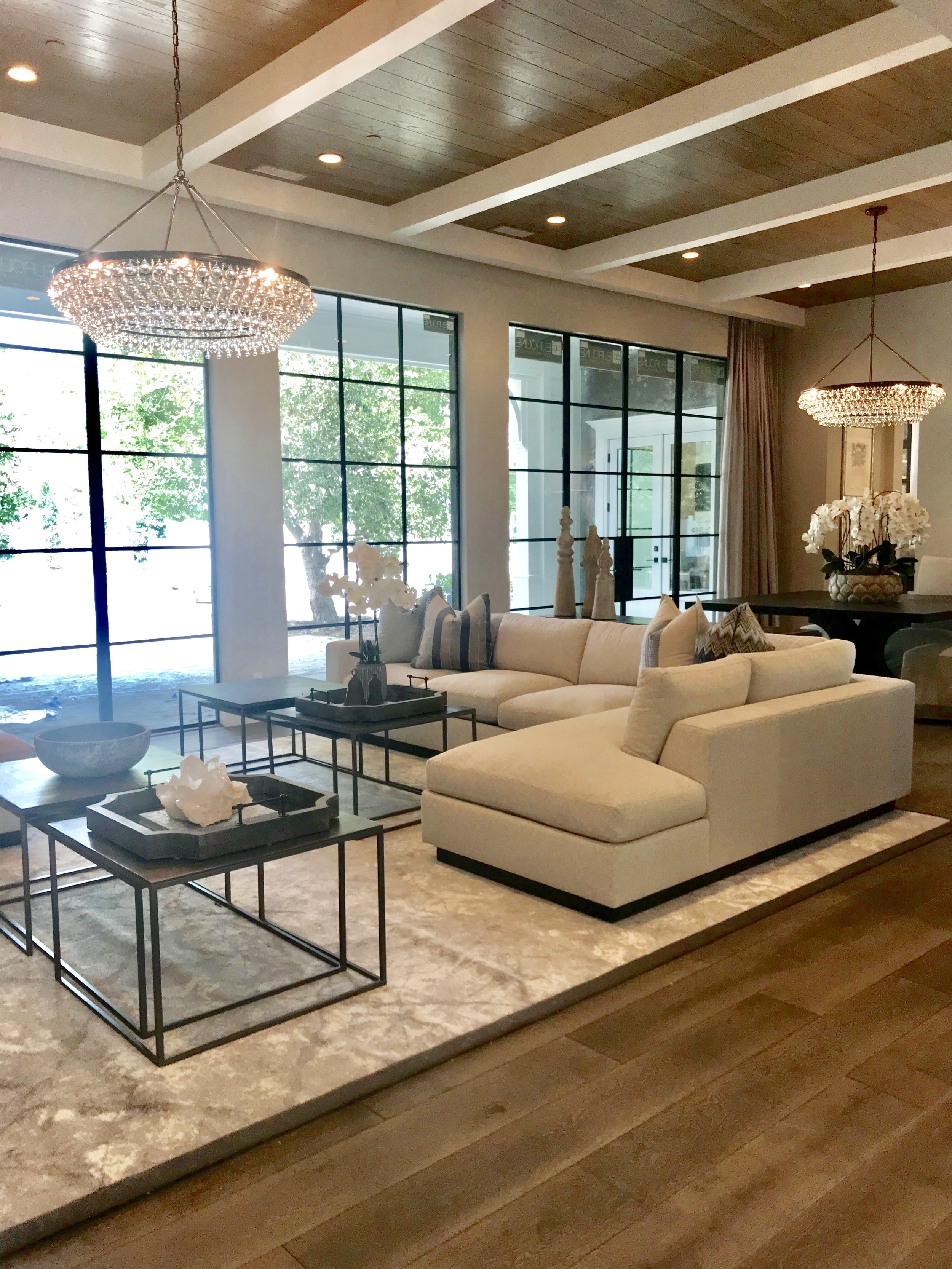 Multiple matte back steel framed doors provide expansive views of the exterior grounds and poolside and the white ceiling beams with warm wood T&G compliment the high ceilings tying in design elements from the entryway.
