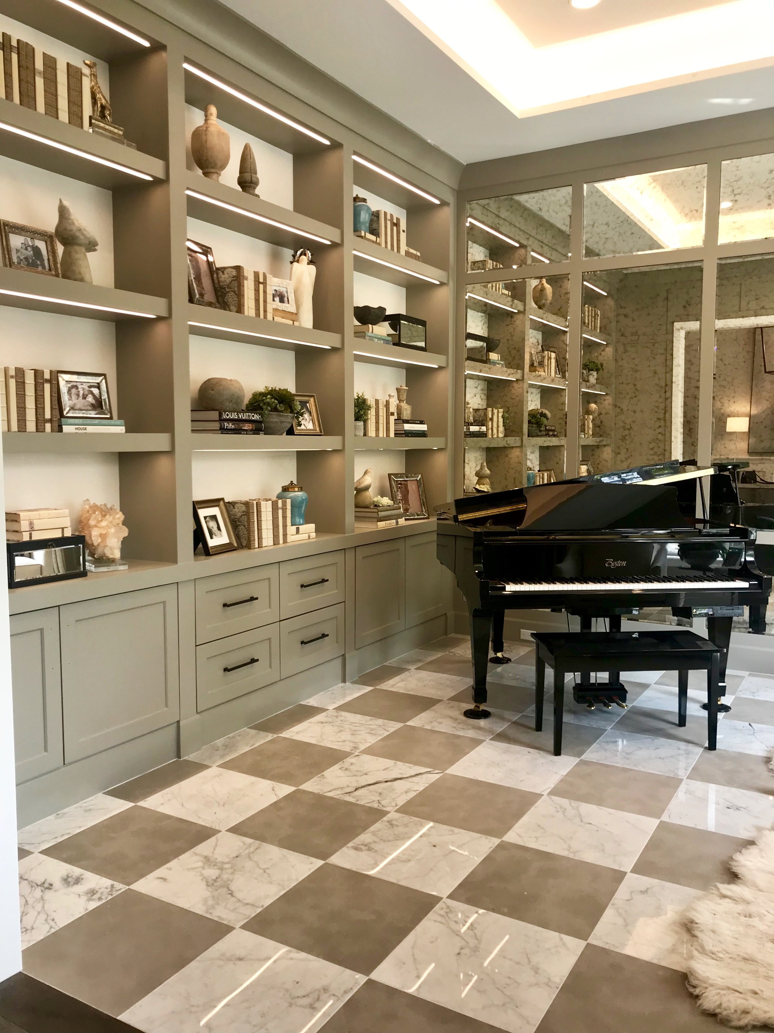 Warm gray wood paneling surrounds the library with beveled antique mirror insets at the focal wall, reflecting elegance at all angles, and a glossy black Boston baby grand piano welcomes guests from the adjacent entry.