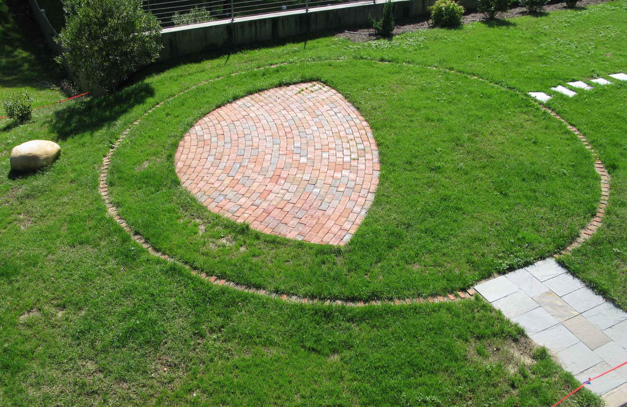 Bricks are inscribed with the names of the Remembered, arrayed in a circle centered on the Memory Stone, a regional glacial anomaly.