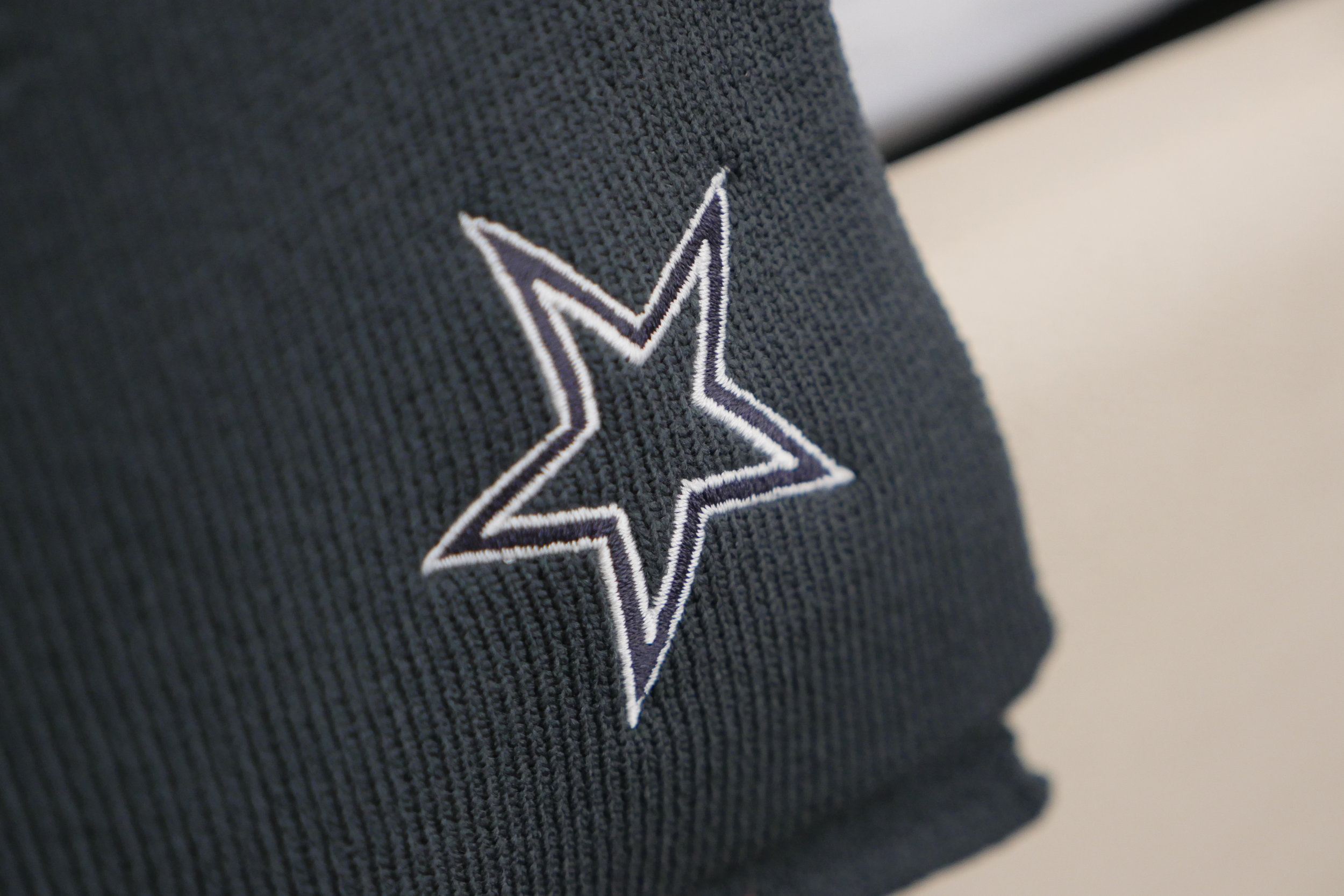 On each bed is a throw with an embroidered Dallas Cowboys star on the corner, by Wilson Associates. The throw is available for purchase in the retail shop.