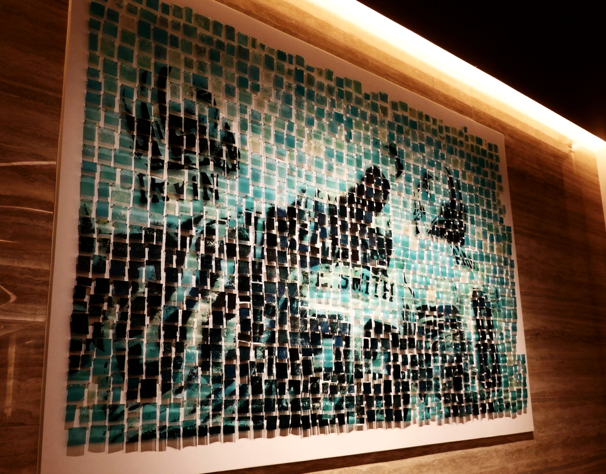 """Using the """"End of Days""""image provided by the Dallas Cowboys Archives,Brandie Grogan of Kalisher created the art installation behind the reception desk,a collage of green-and blue-hued resin squares."""
