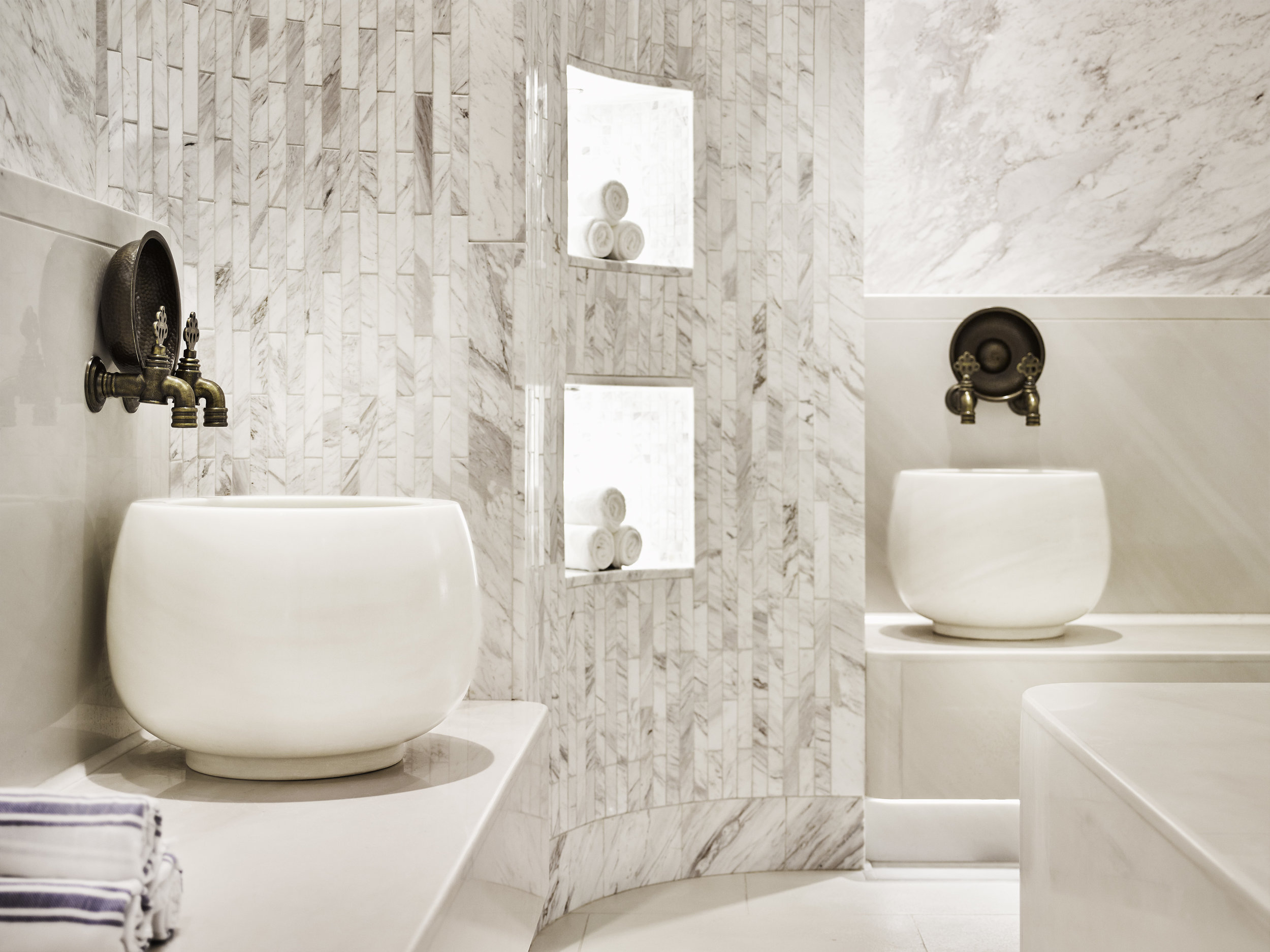 """This traditional Turkish """"Hamam"""" spa features white-on-white, marble-clad walls and benches, finished with traditionally inspired Turkish faucets and hardware."""