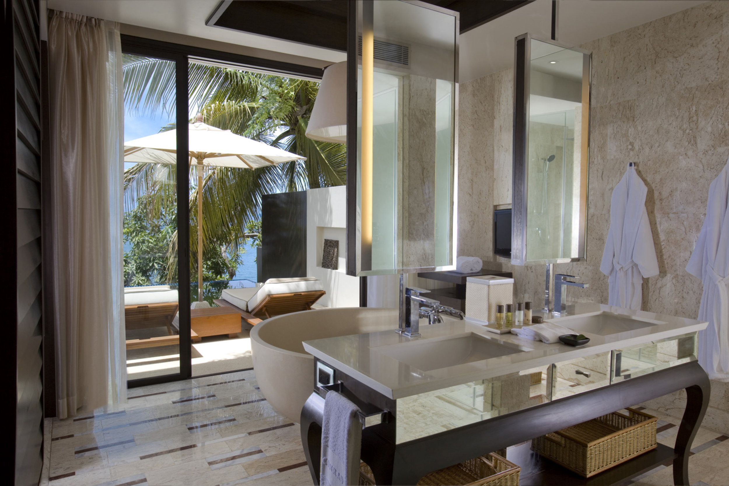 The main feature of the villa is the sizable spa-inspired bathroom that is fronted by floor-to-ceiling glass doors that open to the private outdoor patio and pool.