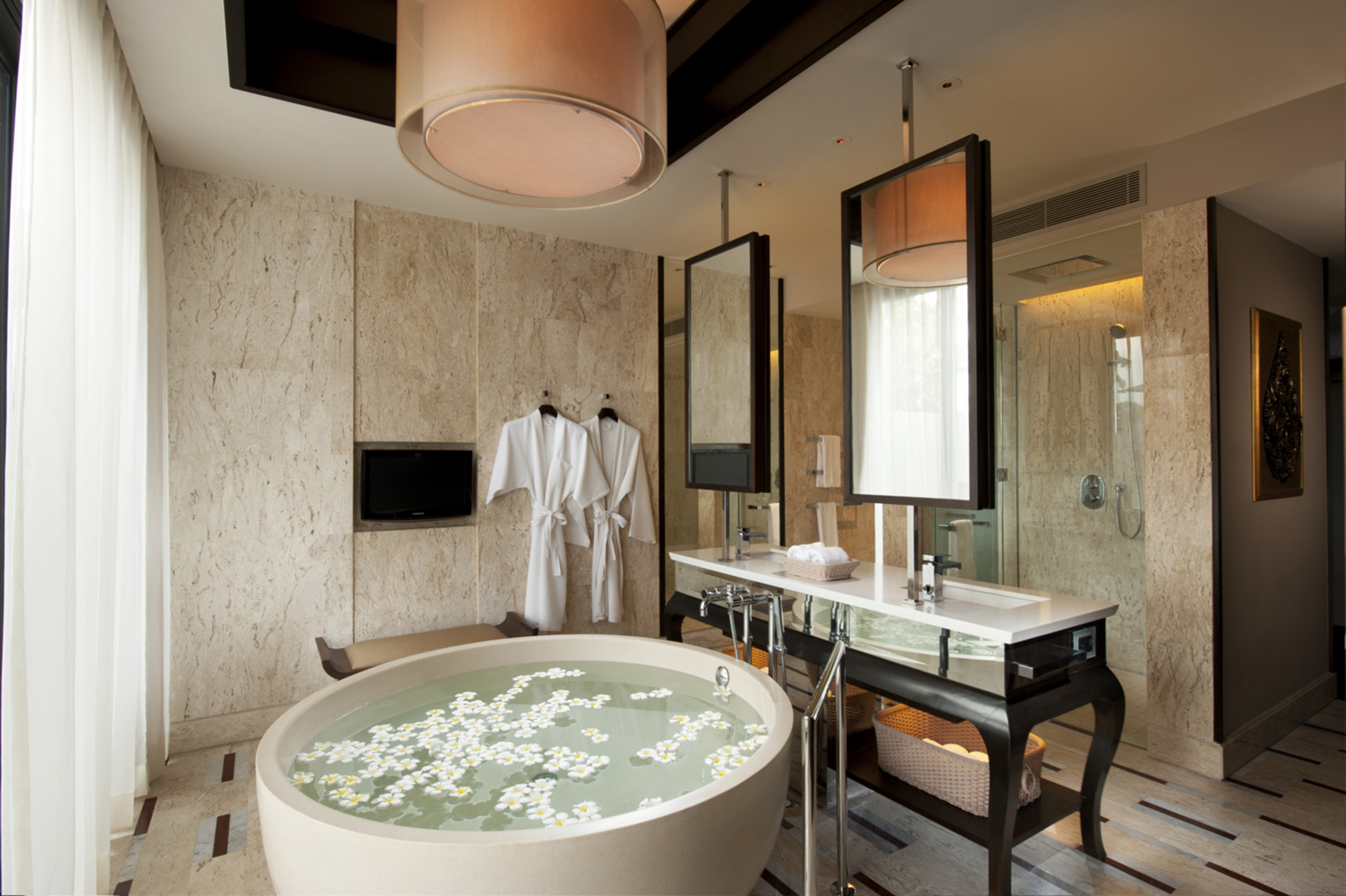 """The vanity counter and standalone bathtub sit on this marble """"carpet"""",adding warmth and a luxurious feel."""