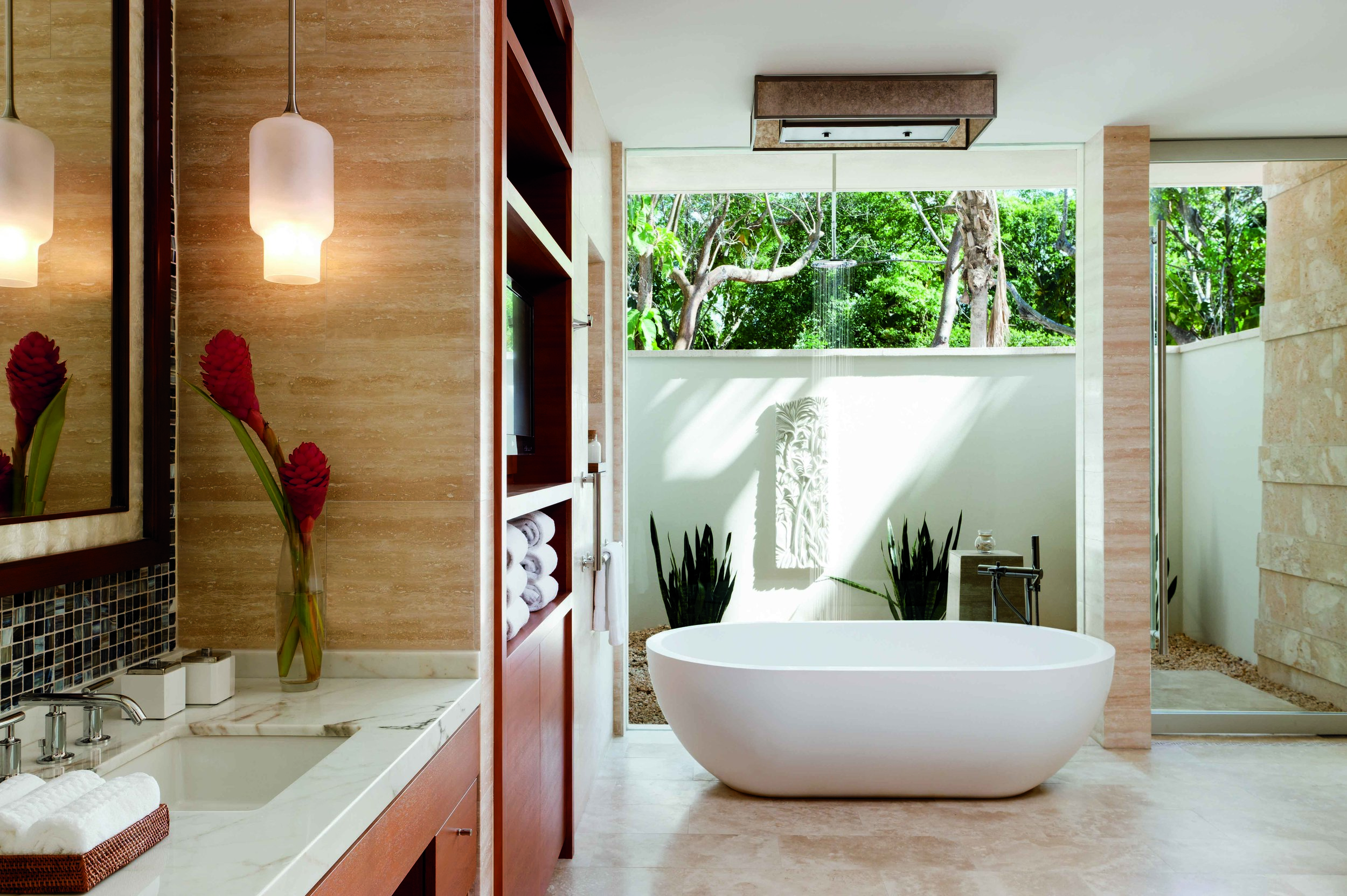 A glass wall divides the indoor bathroom and the private shower garden, which is positioned on a pebble floor.