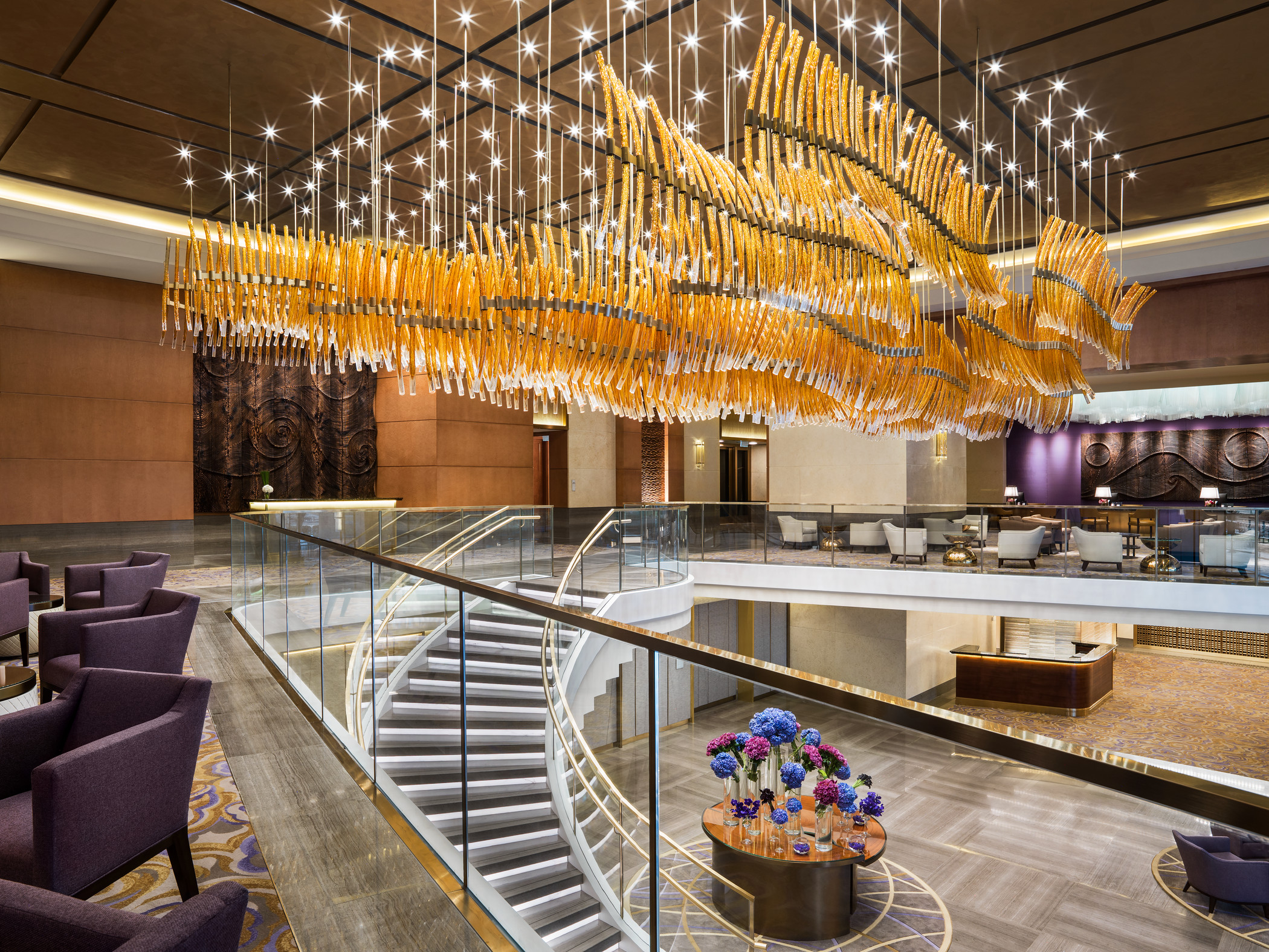 The lobby's sweeping staircase flaunts a dramatic air with illuminated amber, bronze and gold blown-glass strands hanging above as a shimmering allusion to ship sails billowing in the wind.