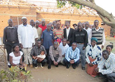 "Lameck, one of the SAFE staff, prayed with several local village pastors  (kneeling in this photo), to have an outreach meeting with 25 chiefs (mostly Muslim) from the Kawiya villages. They decided to show them the ""Magdalena"" file that portrays Jesus' love and respect for women.  Muslim men regard women as second-class people in the community. After the film it was awesome for Lameck to hear chiefs  (standing in above photo)  praying and asking God to forgive them for their wrong attitudes.  One chief commented, ""What we saw in the film is what is happening in our communities … so we would love for you would show the film to all the people we are looking after so they would also turn from this behavior as we have now decided to do."""