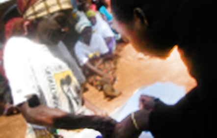 Precious Ntibula, our new Monitoring and Evaluation officer, helping a gogo sign for the seed and fertilizer money