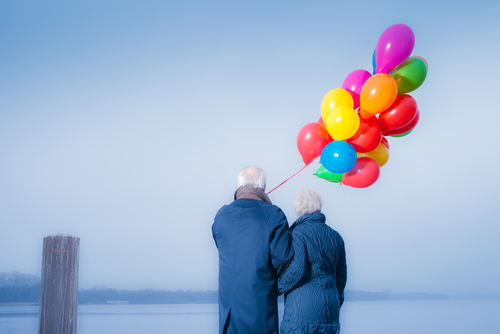 Senior couple with colorful balloons on the Lake