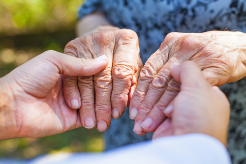 Close up medical doctor holding senior woman's shaking hands