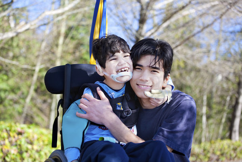 disabled boy wheelchair hugging brother