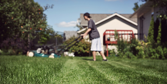 teenage boy mowing lawn