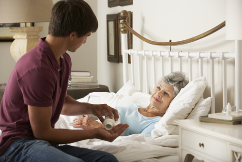Teenage Grandson Giving Grandmother Medication In Bed At Home