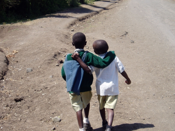 Kids from Mbita Primary walk arm in arm along a long dust-road like the one that would take them to the soccer field.