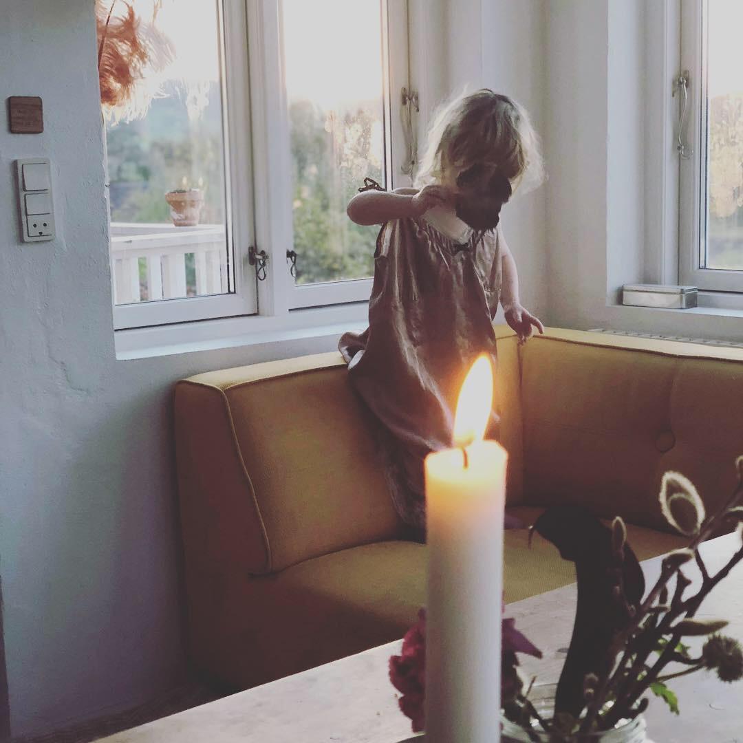 Min datter sol, dansende med et blad i vores hjem i Laven.