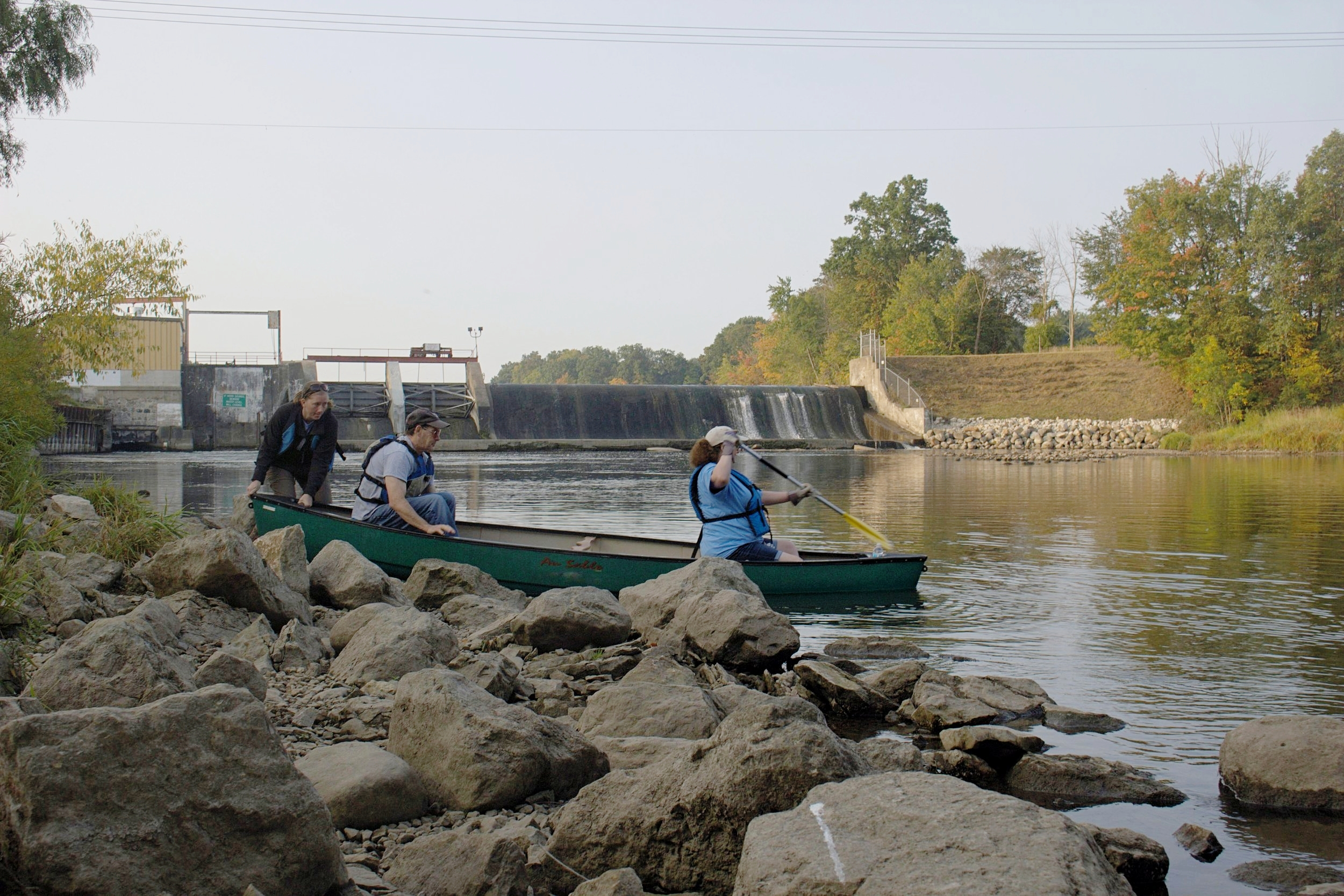 Six canoes and two kayaks launched from the public access by LaBarge Dam, seen in the background of this photo. In the foreground, Bill Sonday and Jenifer Werdon get help launching from Korie Ebenstein. This was Ebenstein's sixth time working with the TRWC, whereas Sonday was on his third year, and Werdon on her first.