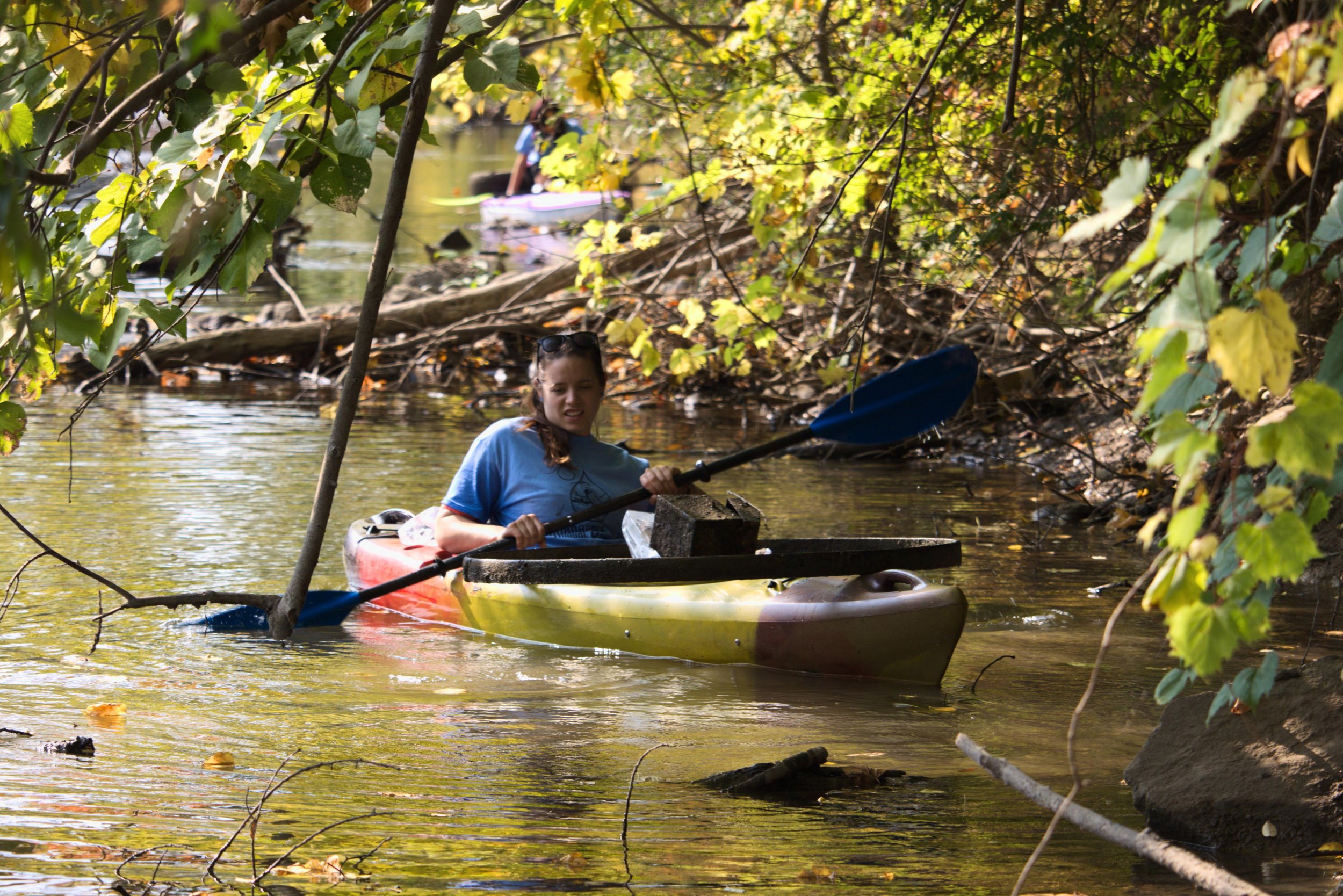 Vanessa Foera maneuvers her kayak through the dead-falls and underbrush along the side of the river. In the middle of the iron hoop on her kayak is an old toolbox that she recovered from the river's bottom. She and her sister, Rachel Frantz, grew up near the Thornapple River and like to help keep it free of pollution.