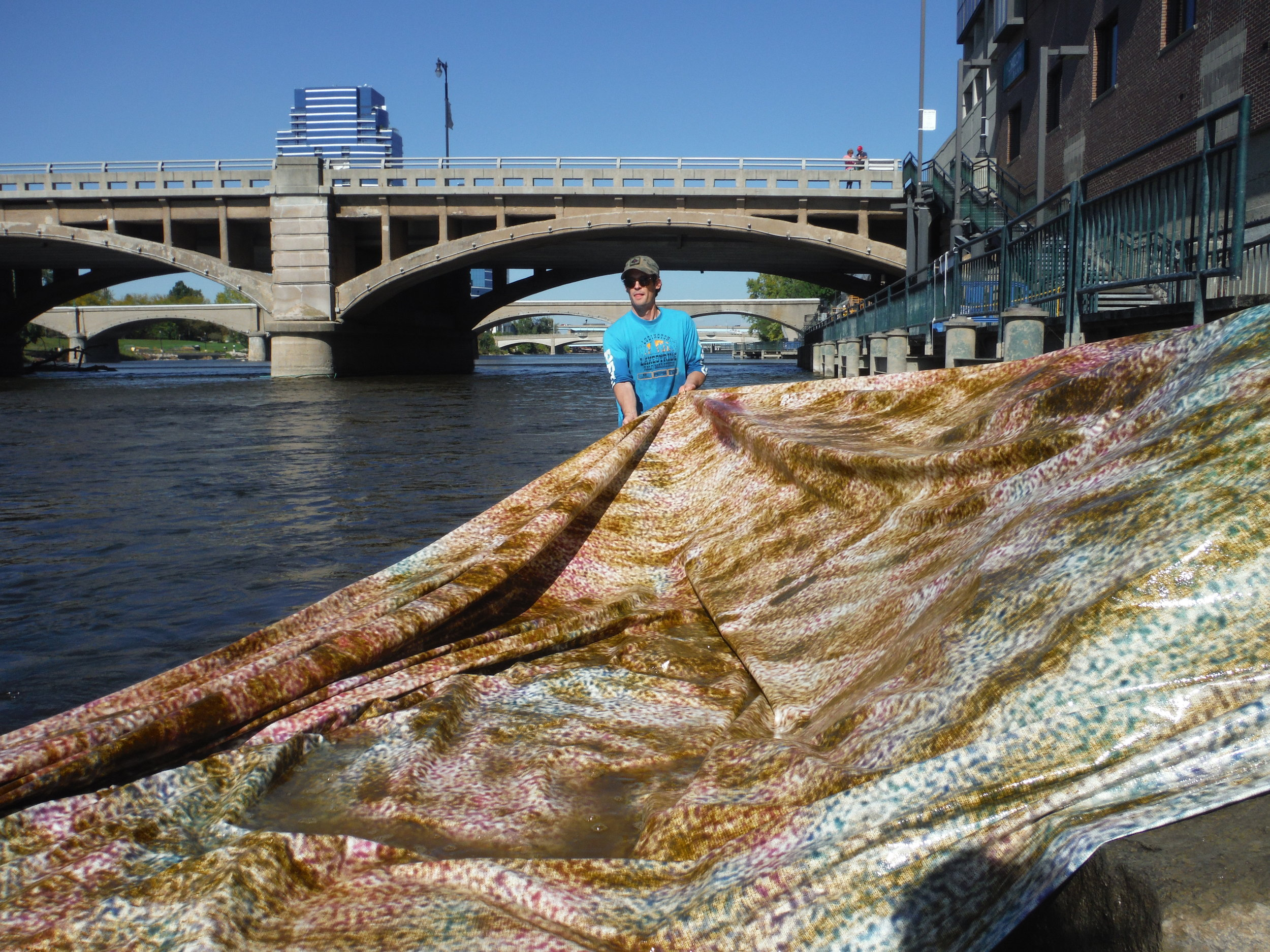 """Ryan Spencer Reed, holding a section of """"Oil+Water"""" as it's dragged out of the river."""