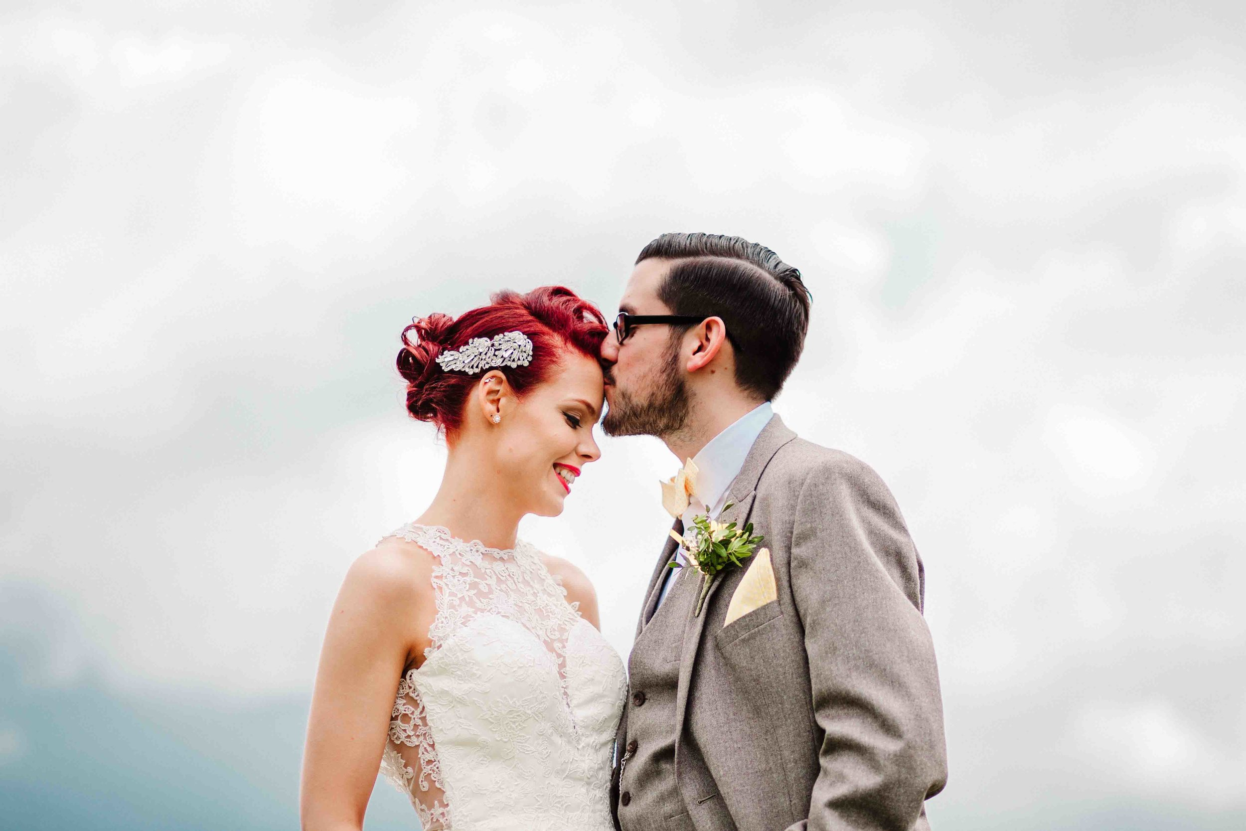 A groom kissing his bride on the forehead