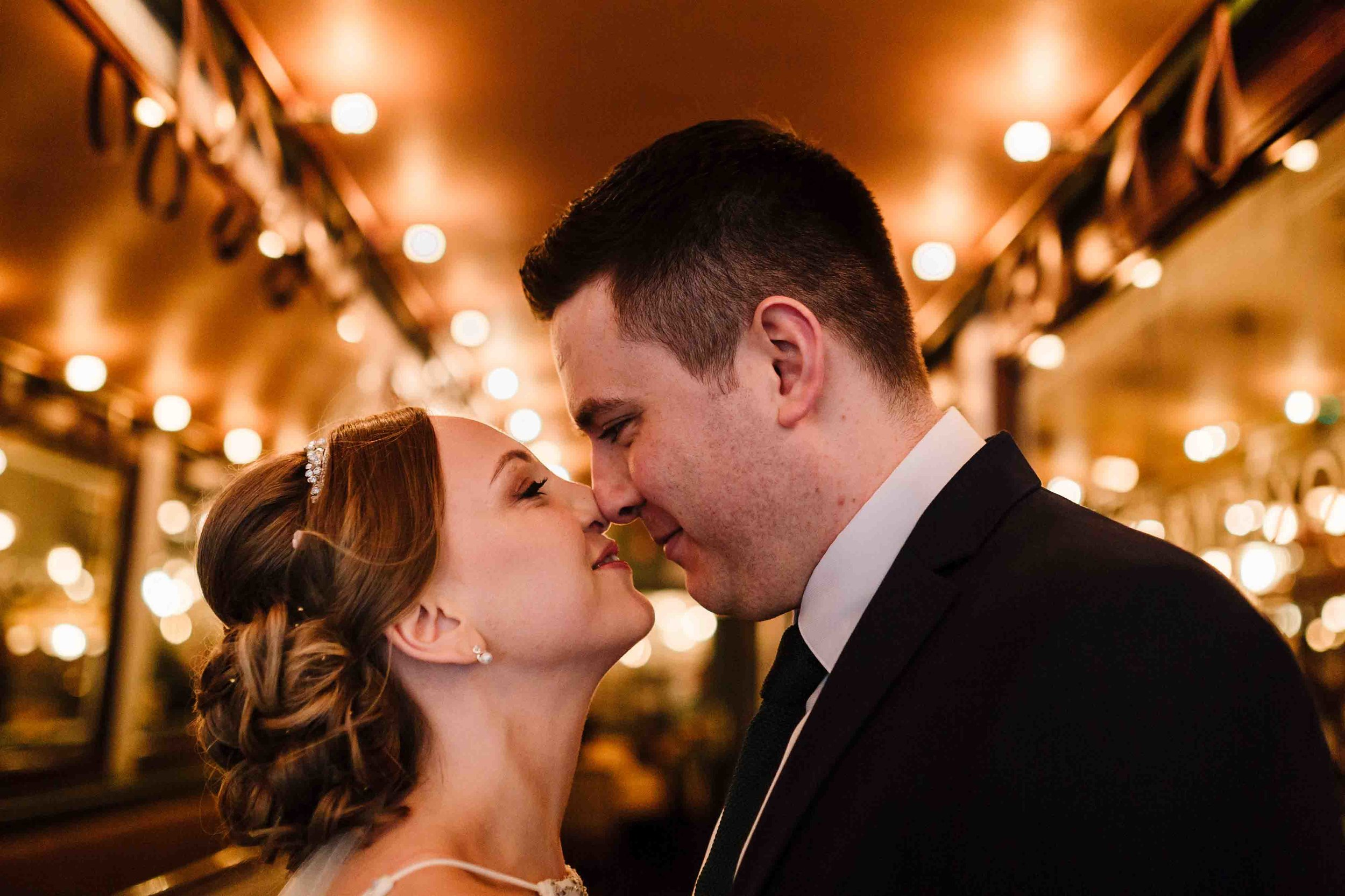 A bride and groom eskimo kissing