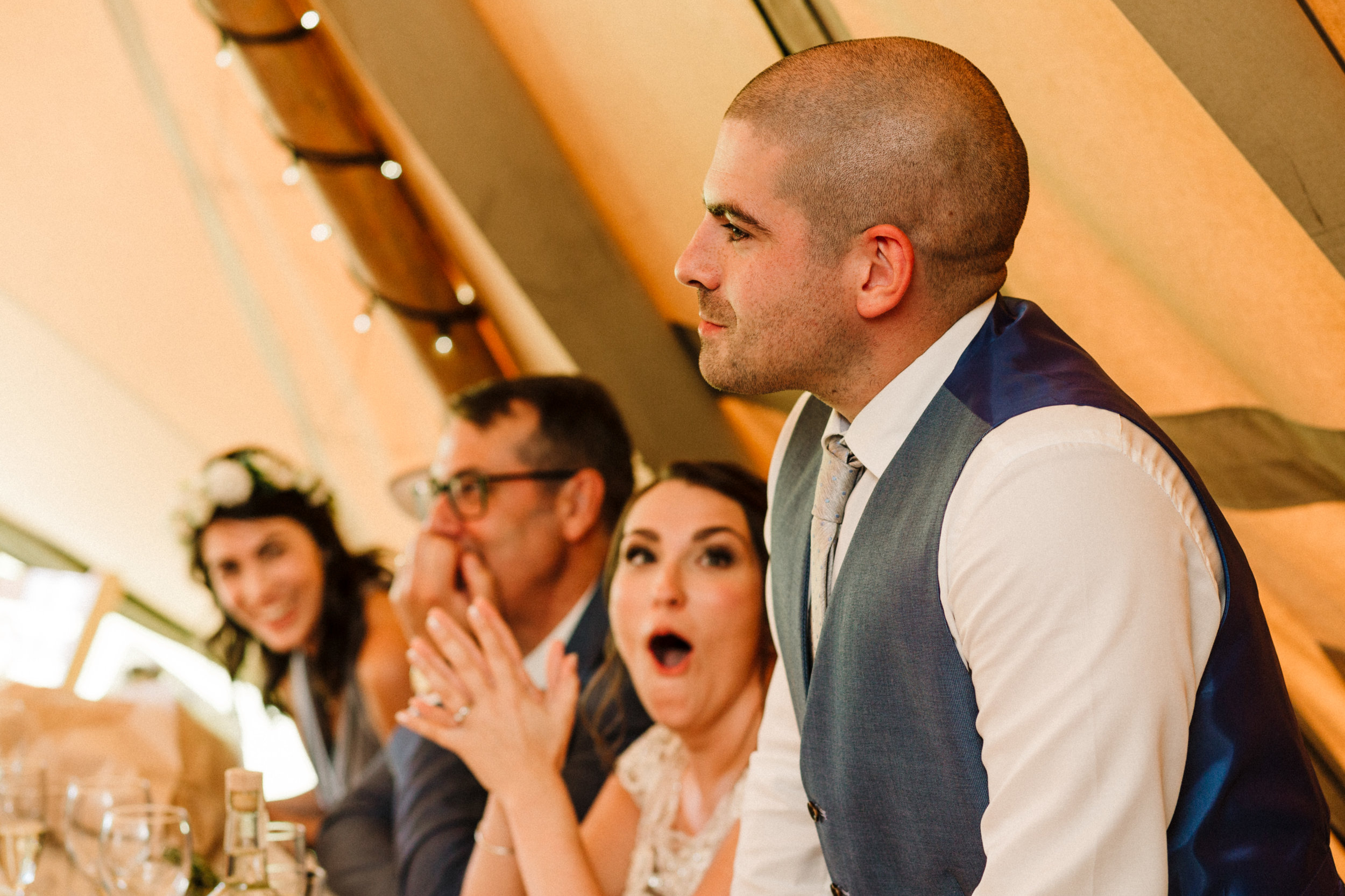 A bride pulling a shocked face during a best man speech