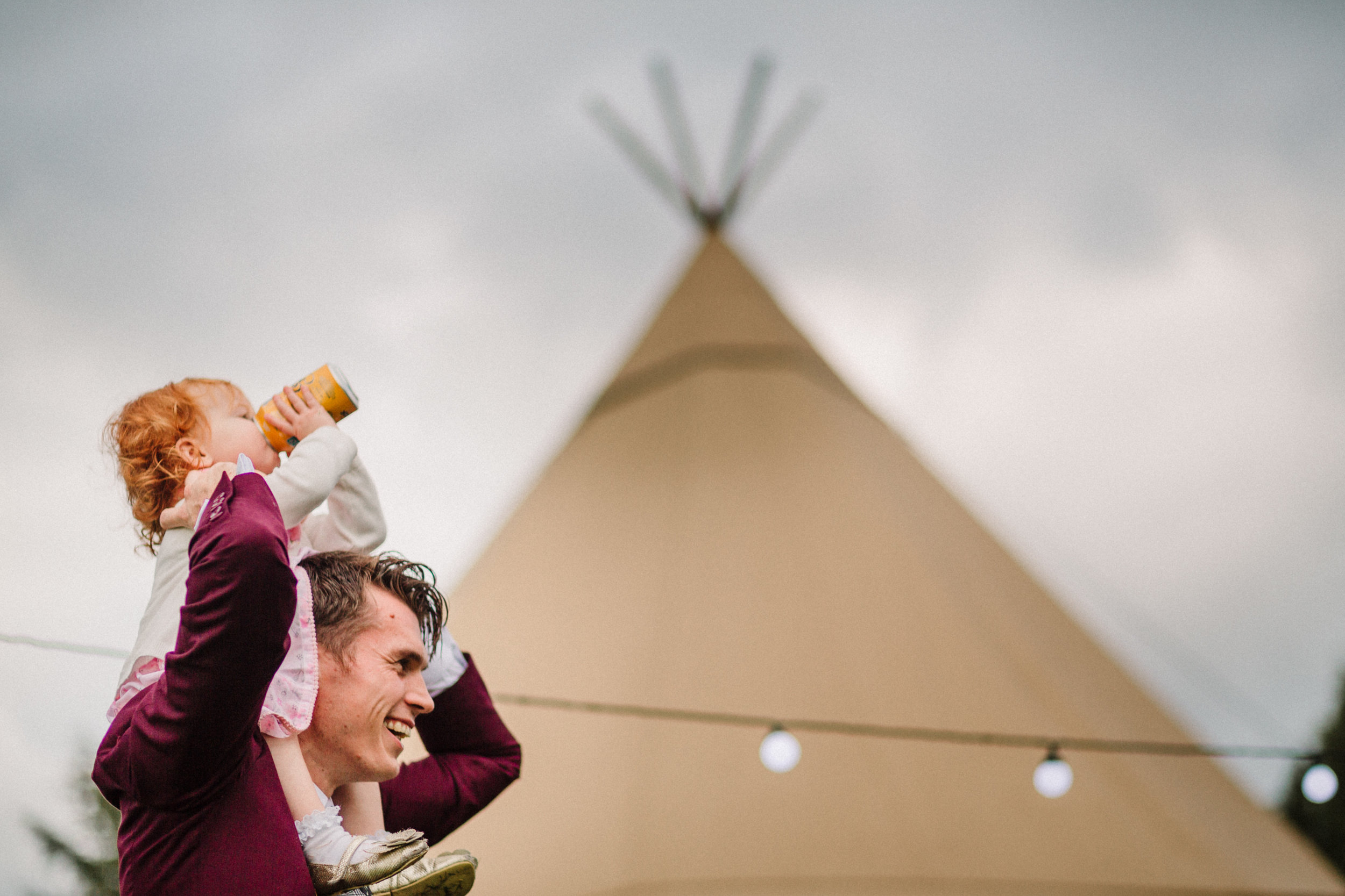 A wedding guest holding his daughter on his shoulders in front of a teepee
