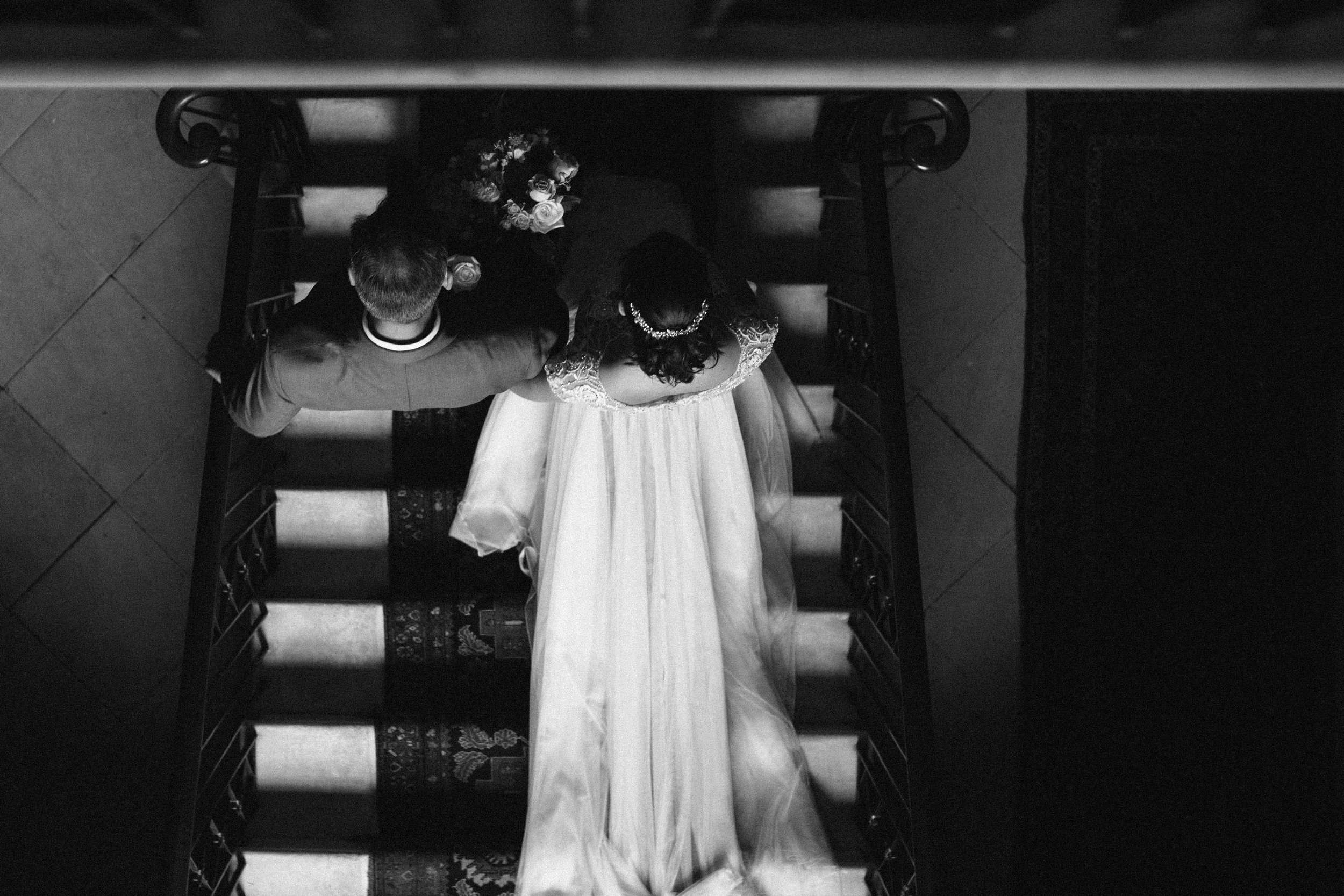 A shot from above of a bride walking down the stairs with her dad