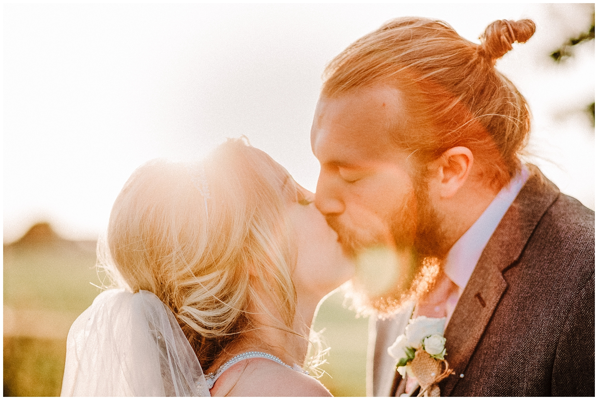 a bride and groom kissing at sunset.jpg