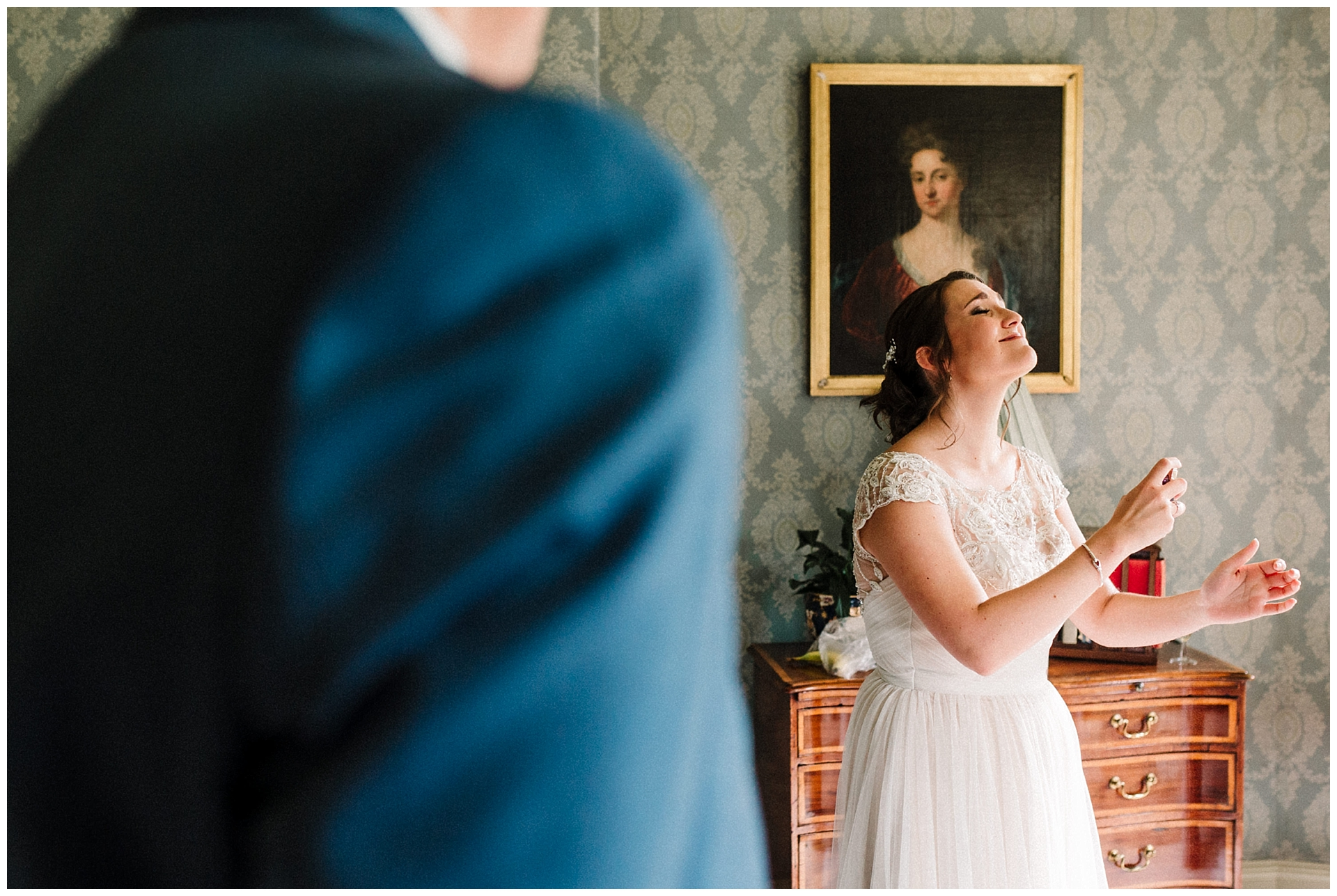 a bride putting her perfume on on her wedding day