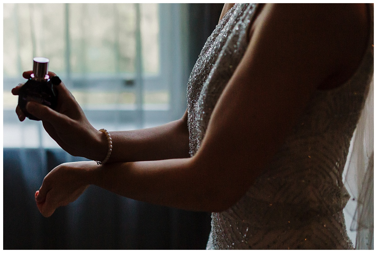 a bride putting perfume on her wrists