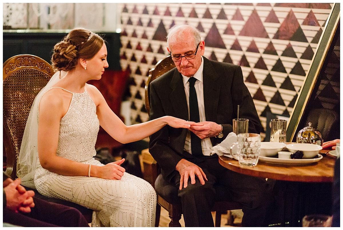 a bride showing her grandad her wedding ring